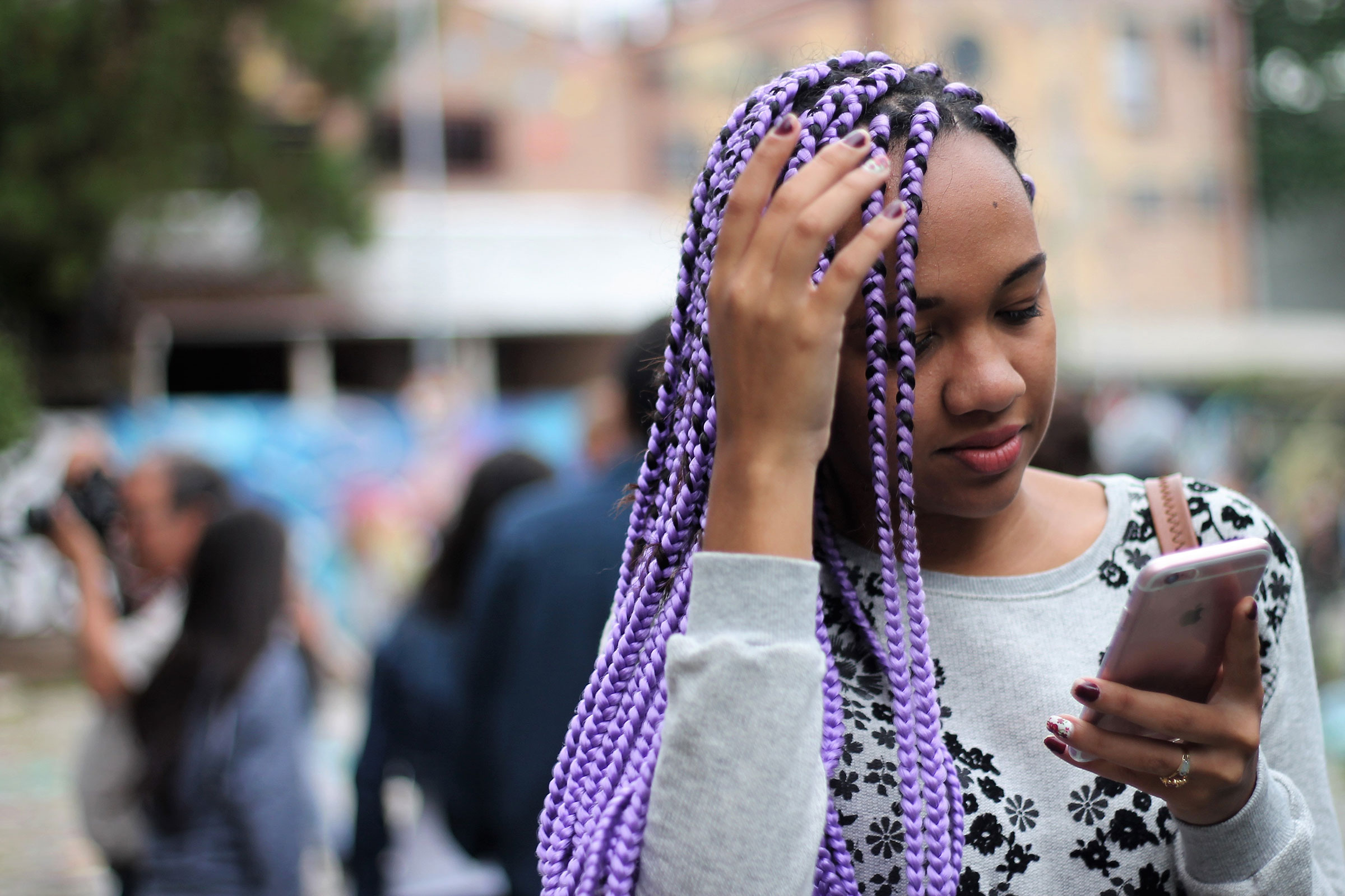 a Black teenager with long, purple hair, stares down at her phone