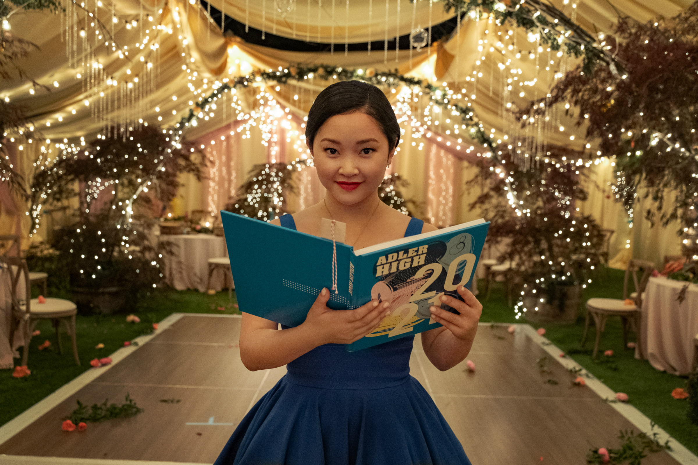 Lana Condor, an Asian teenager with short, black hair, holds a turquoise book while wearing a turquoise dress at prom in To All The Boys: Always And Forever