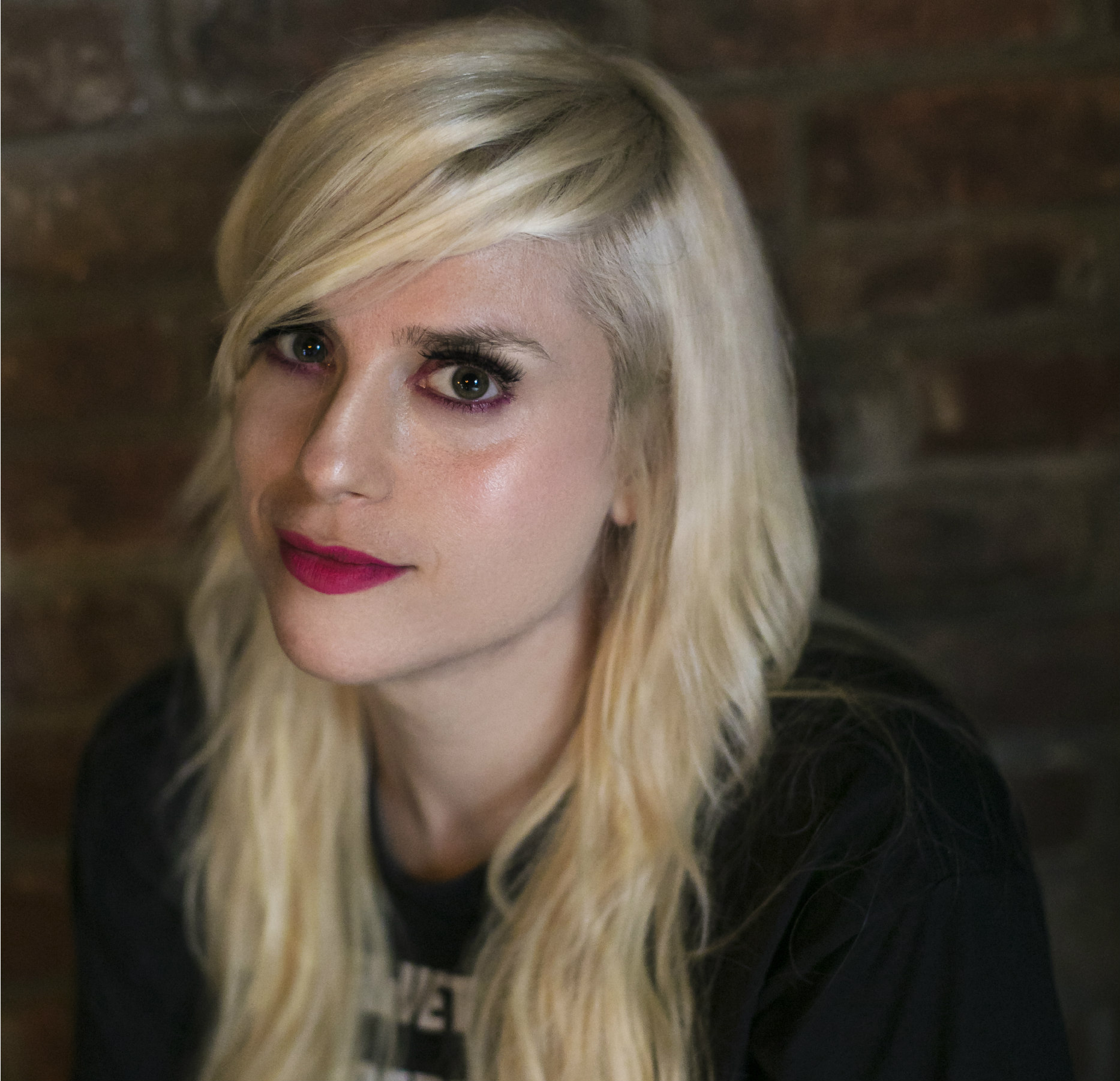 a white woman with shoulder-length blonde hair and red lipstick wearing a black t-shirt