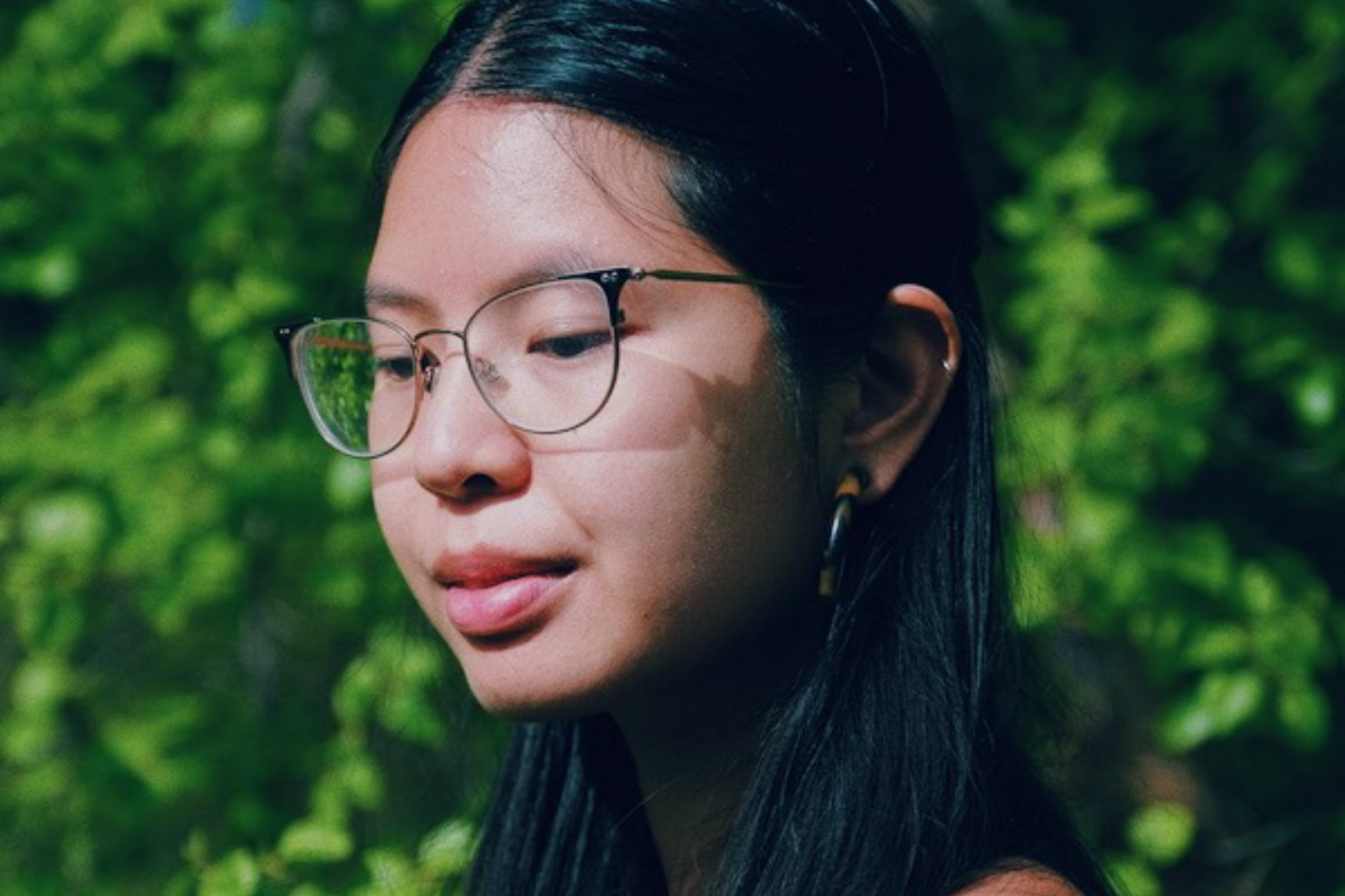 Larissa Pham, an Asian, pensive woman wears wire rim glasses in front of greenery