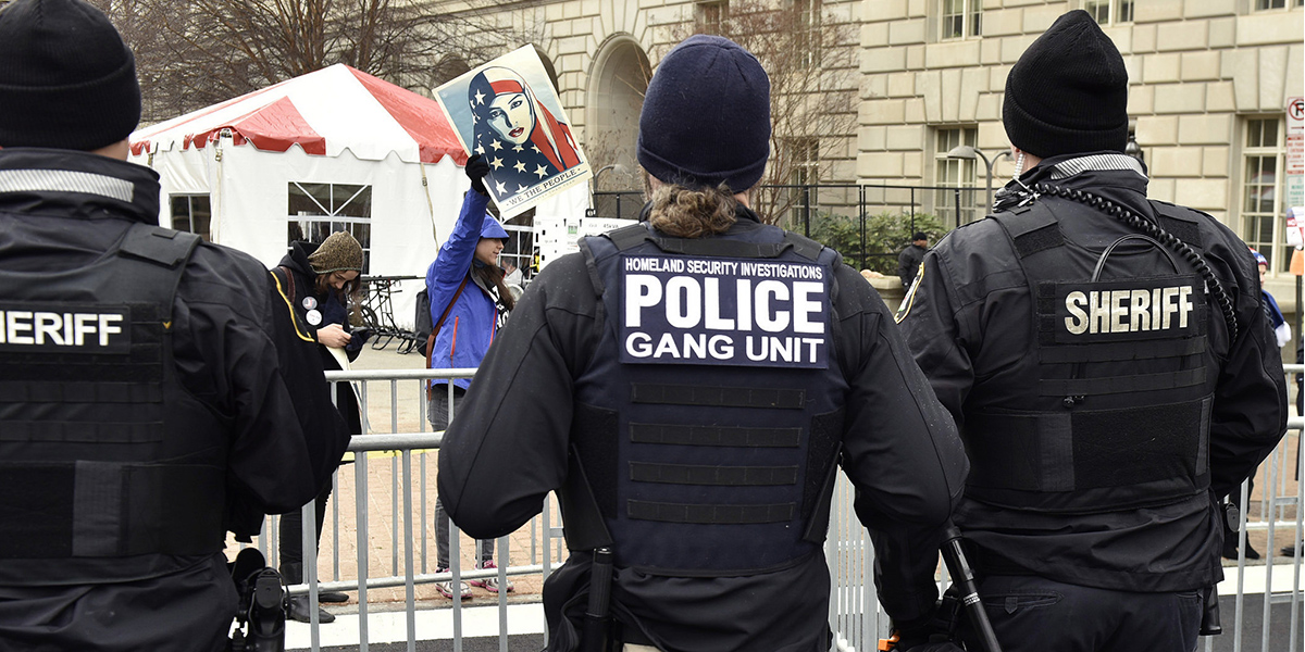 Law enforcement with their backs turned to the camera while people protest Trump's inauguration