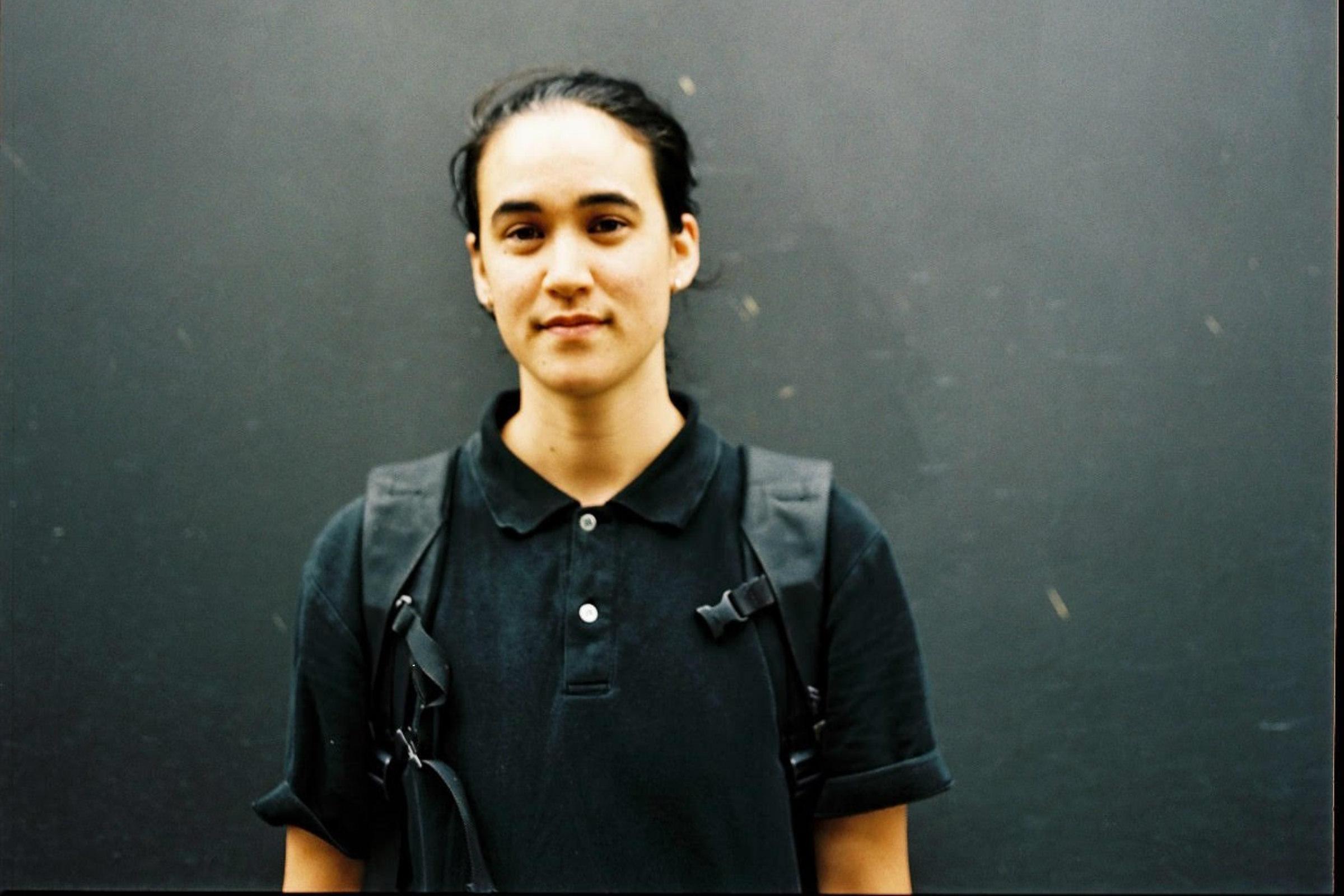 Lee Lai, a young Asian person wears a backpack and polo shirt