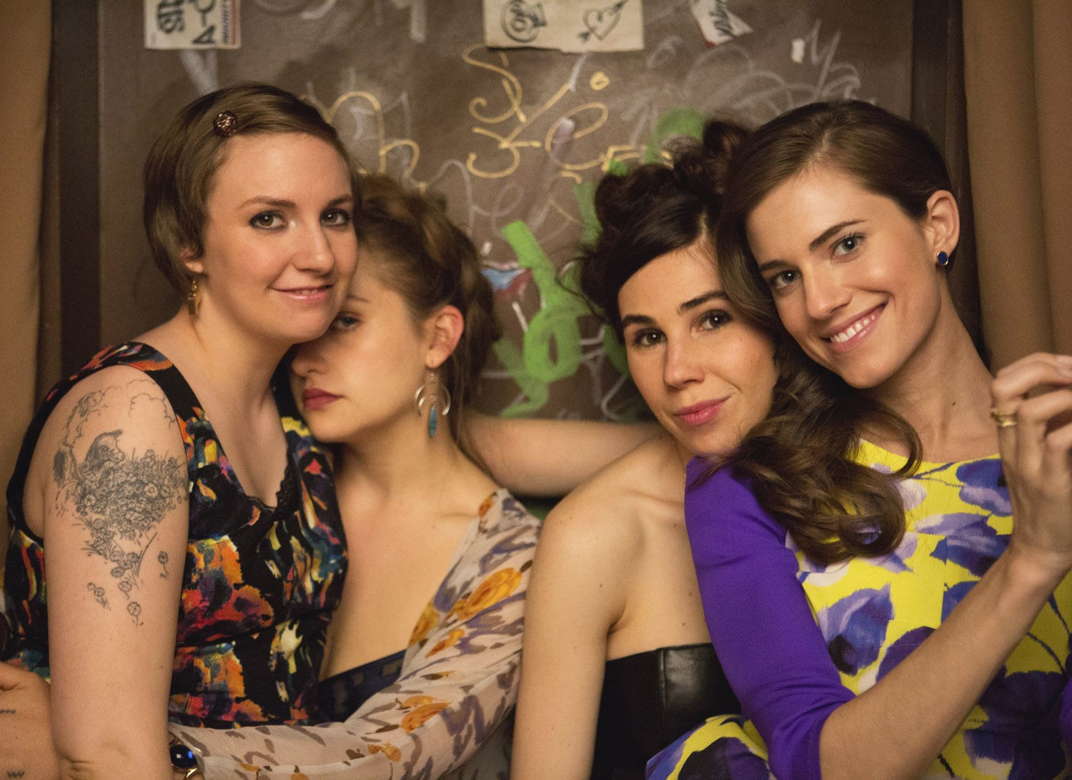 four white girls in their 20s pose for photos in a booth together on Girls