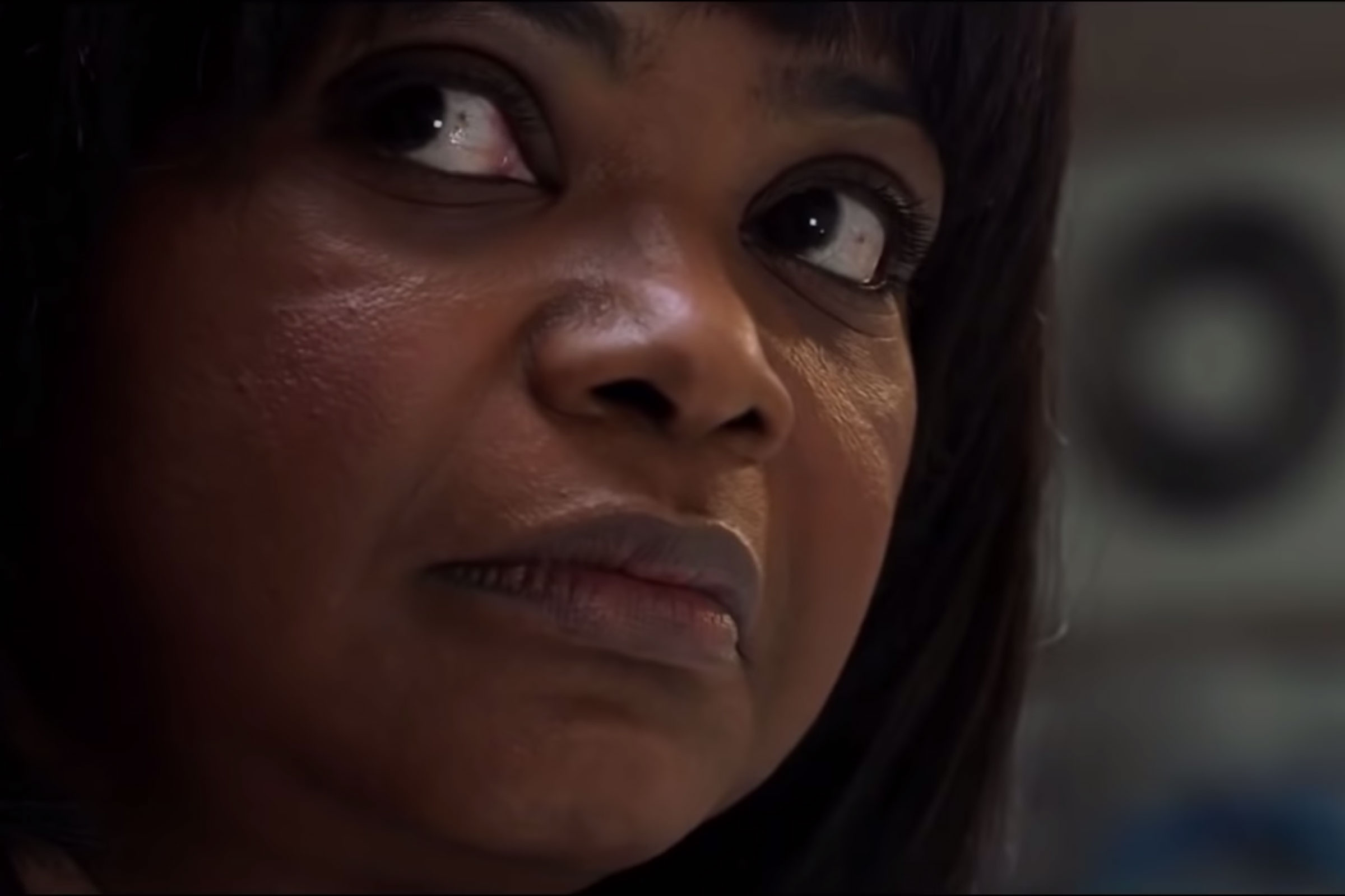 close-up photo of a Black woman with short, black hair looking ominously off-screen