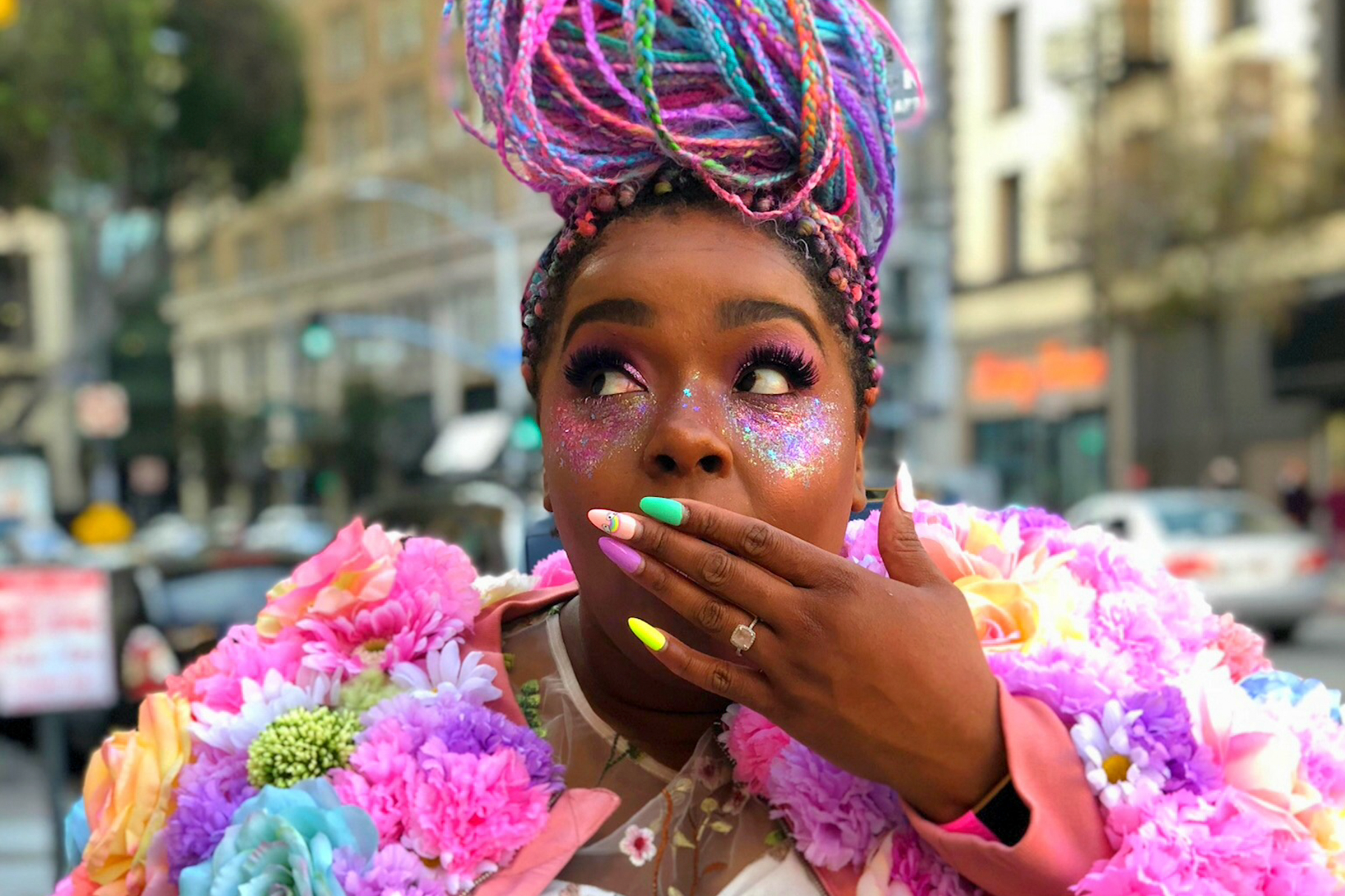 Amina Mucciolo, a Black person with colorful hair pulled into a bun, poses on a street corner with their hand over their mouth