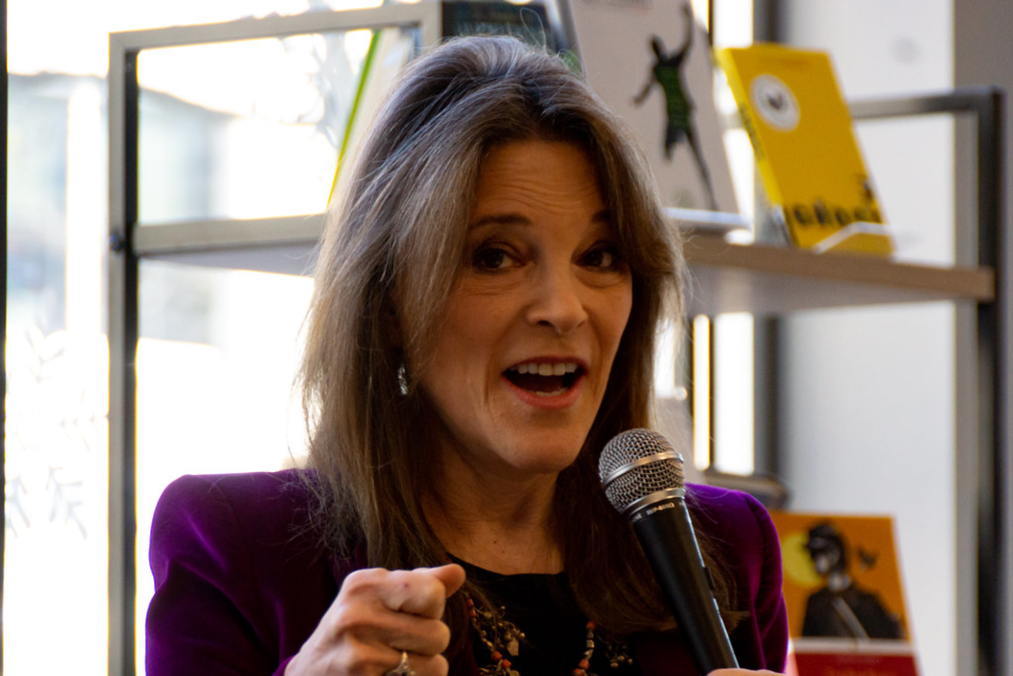 A photo of Marianne Williamson, a white woman, giving a speech in Manchester, NH. She stands at a mic and gestures toward the audience.