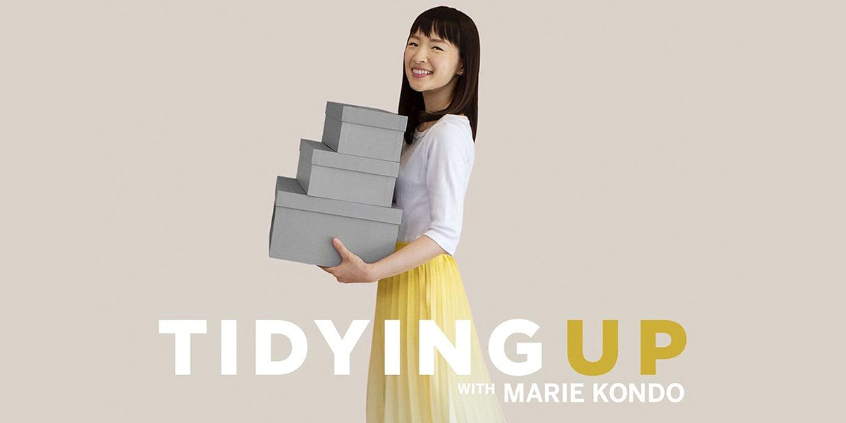 """Marie Kondo holding three gray boxes against a tan background with the title """"Tidying Up with Marie Kondo"""""""