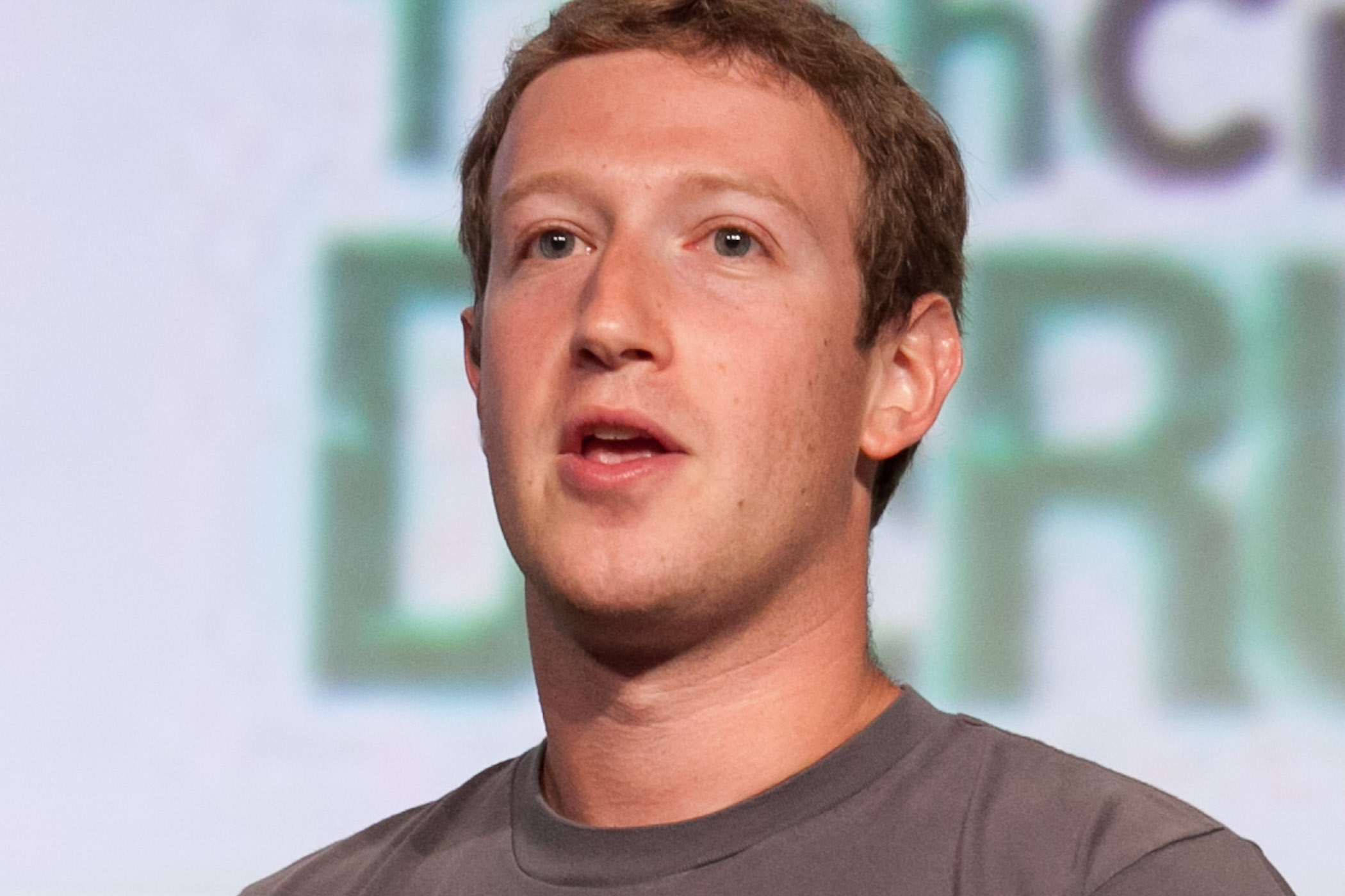 Facebook CEO Mark Zuckerberg is a white man with light eyes and short hair. He speaks on stage.