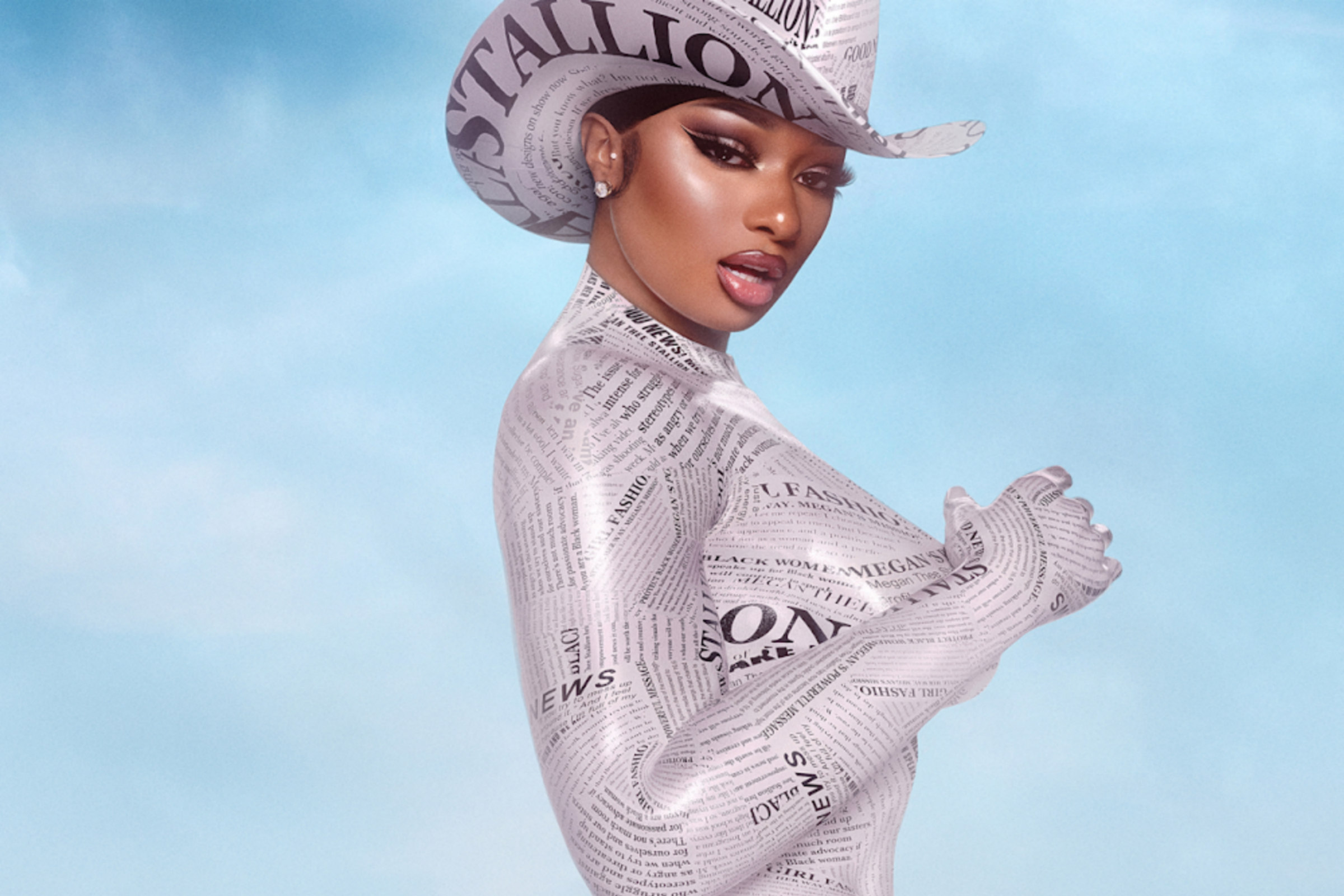 Megan Thee Stallion, a brownskinned Black woman, poses against a light blue background in a newspaper-covered outfit and cowboy hat