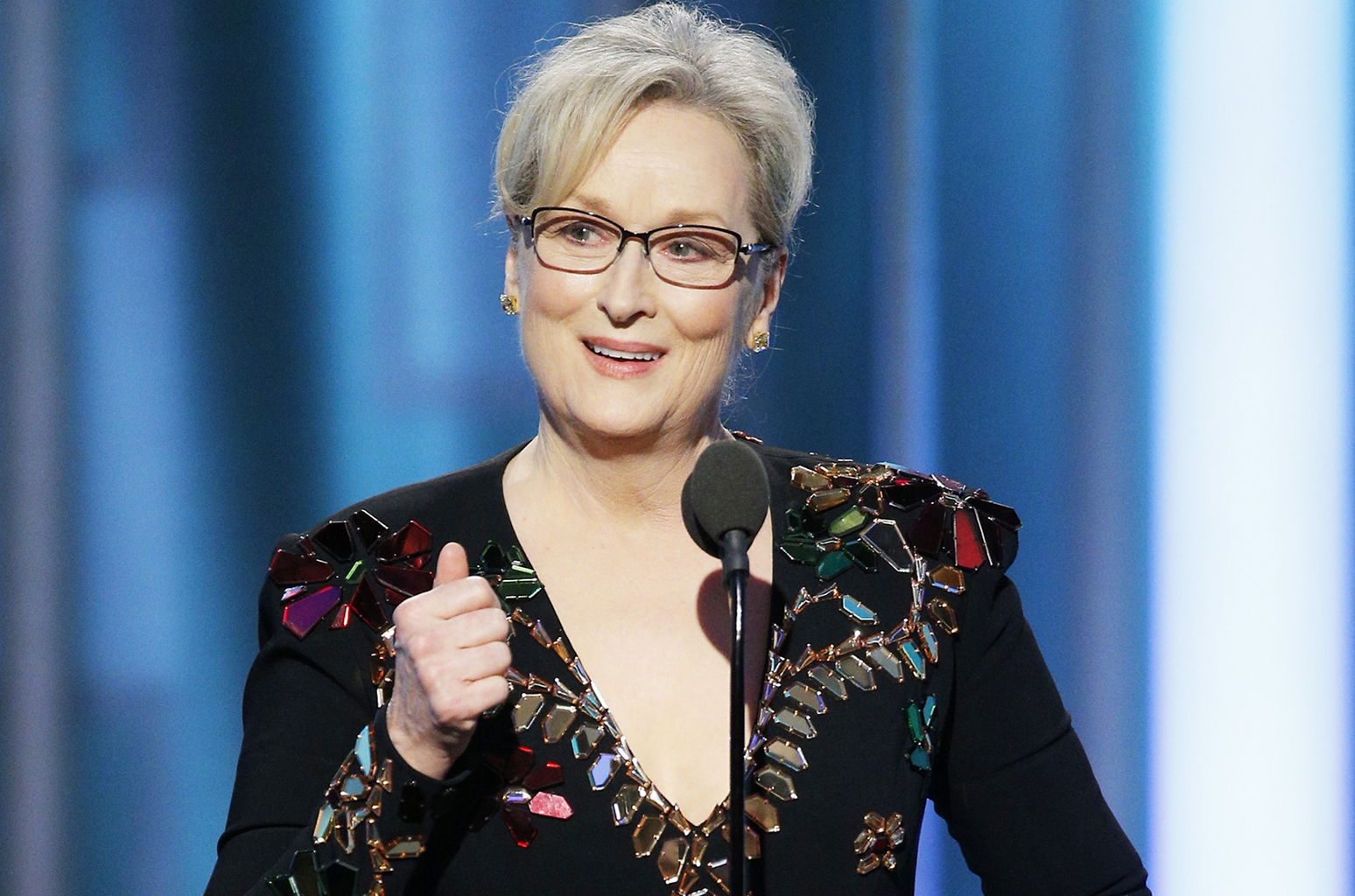 Meryl Streep, an older white woman with gray hair and glasses, delivers a speech at the Golden Globes