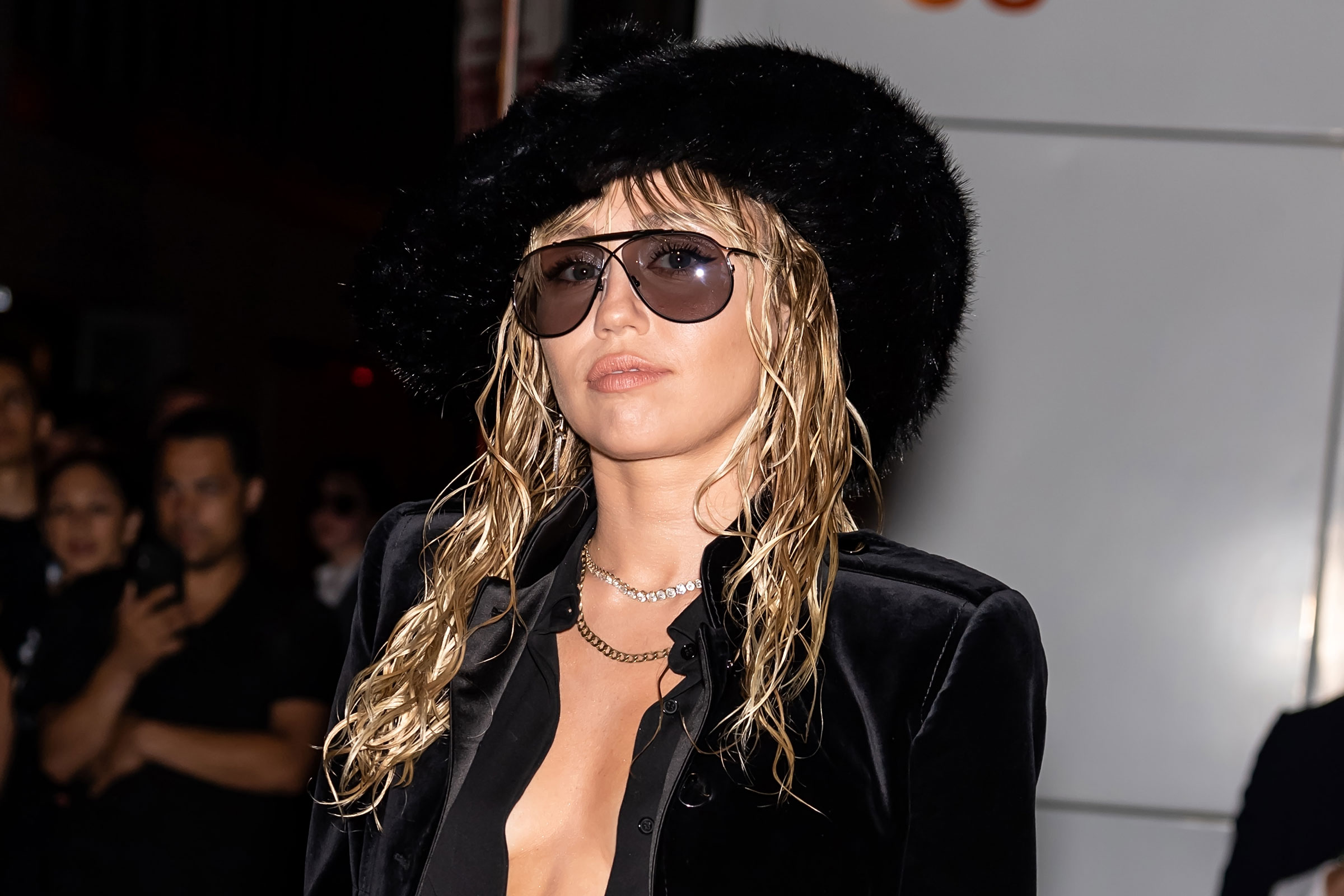 Miley Cyrus, a thin white woman, wears a black blouse and black cowboy hat.