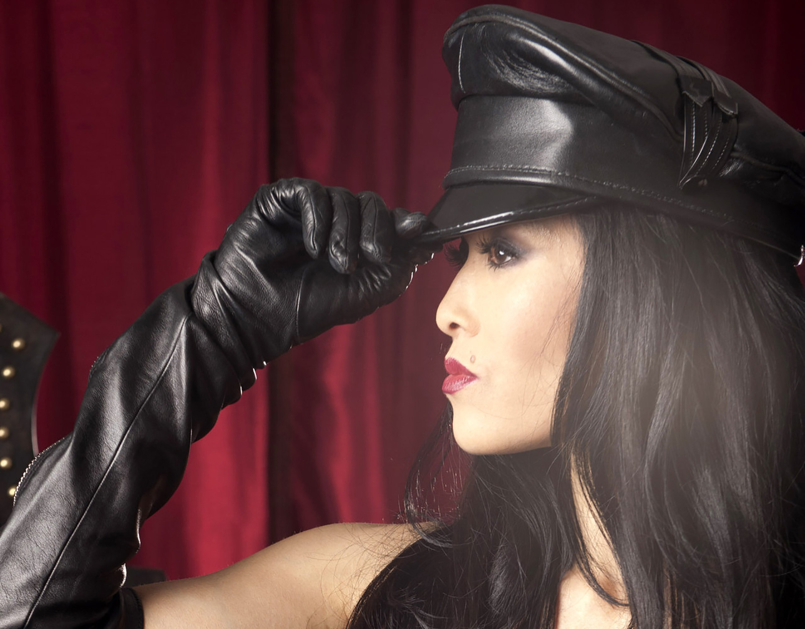 a profile of an Asian dominatrix with long black hair who's wearing red lipstick and a black hat
