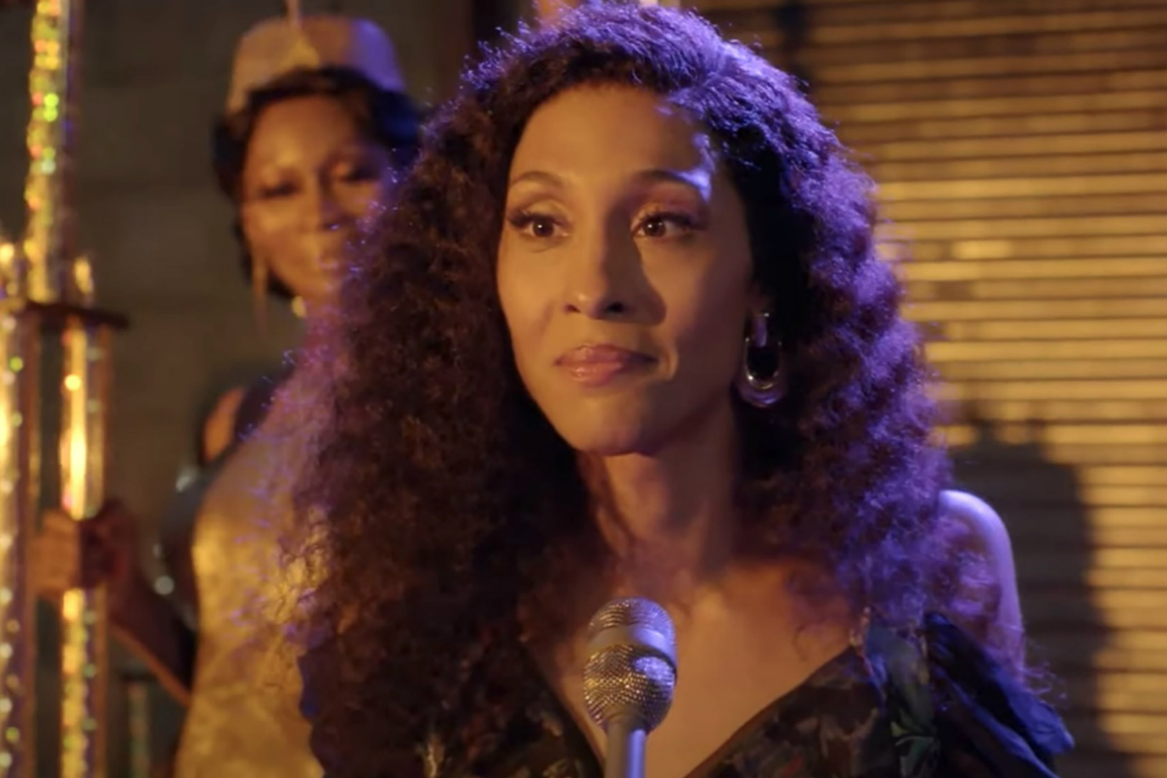 Mj Rodriguez as Blanca, a Black trans woman with long black hair speaks into a microphone on Pose