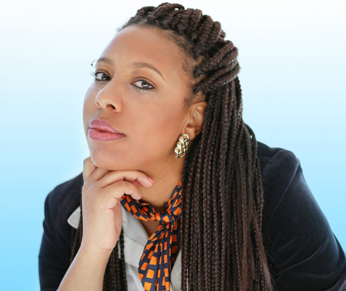 Author Morgan Parker, who is a Black woman, wears a black blazer, white shirt, and an orange scarf. She leans on her hand and looks at the camera.