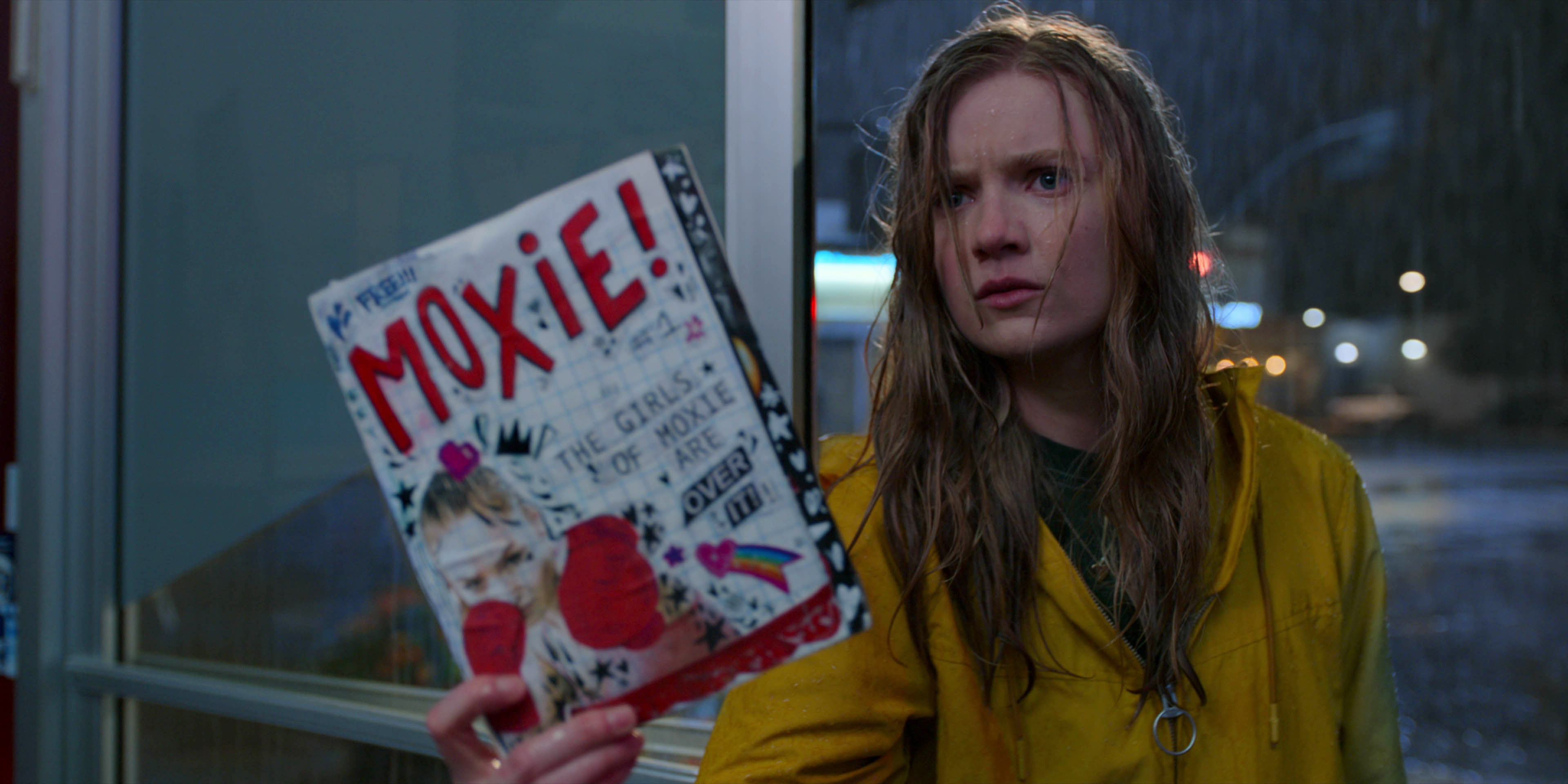 A young white girl wears a yellow raincoat and steps into a store while holding a zine.