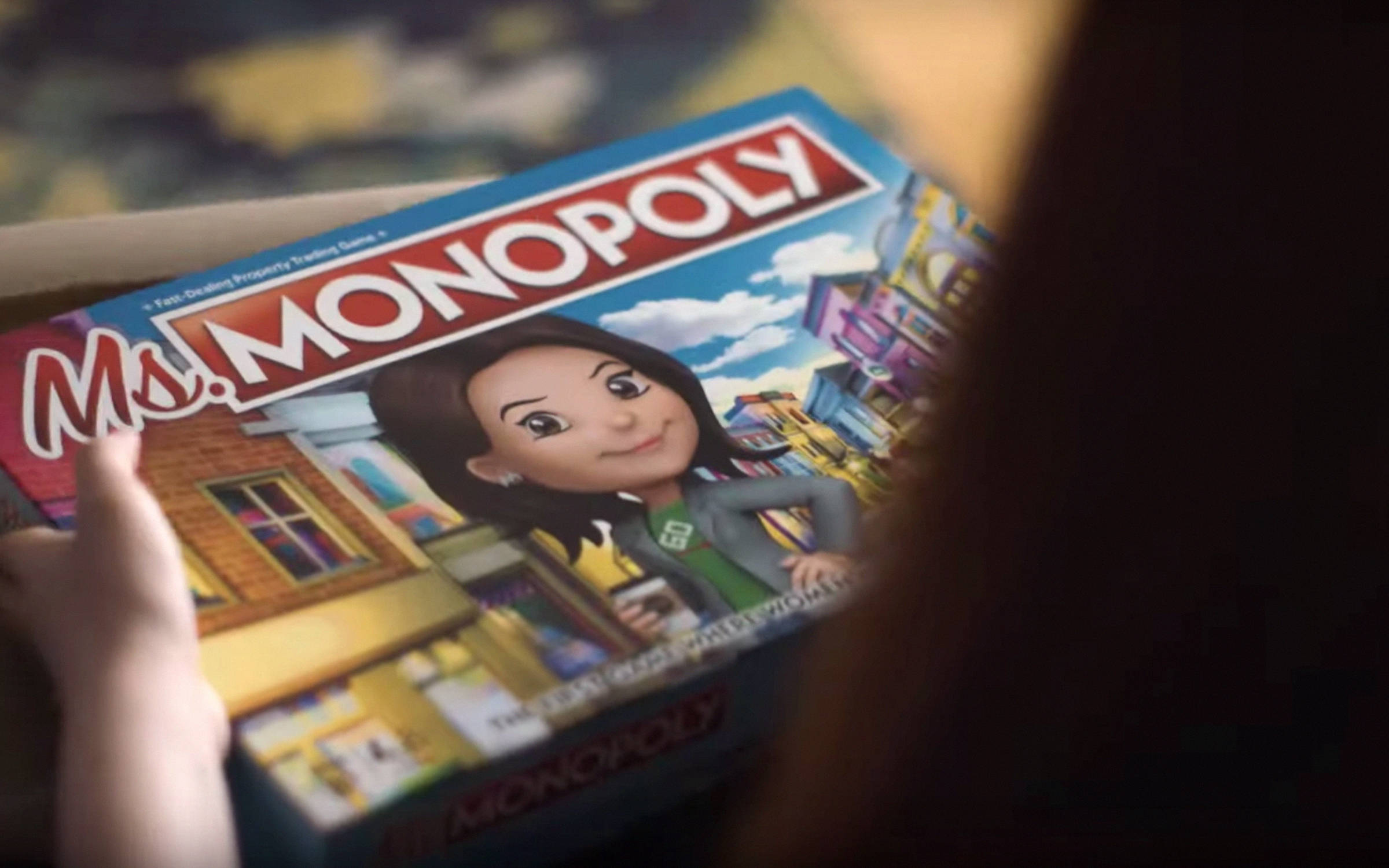 A photo of Ms Monopoly, a new board game from Hasbro. The game features an illustrated woman, presumably white, holding a coffee cup and staring at the camera with a soft smile.n