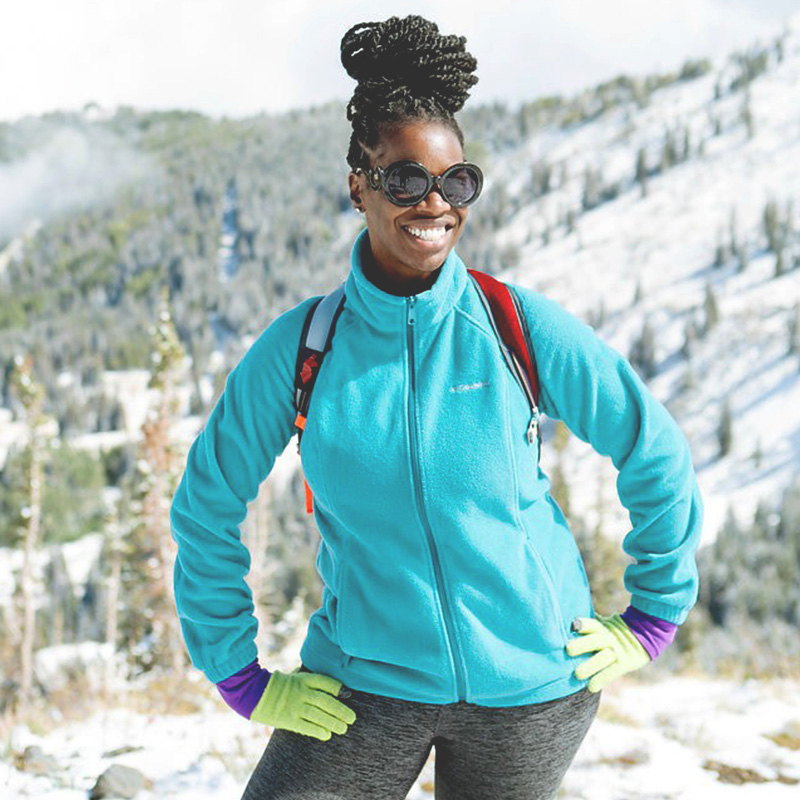 Photo of a Black woman with long braids in a bun, smiling and standing on a snowy mountain, wearing sunglasses and a colorful blue fleece