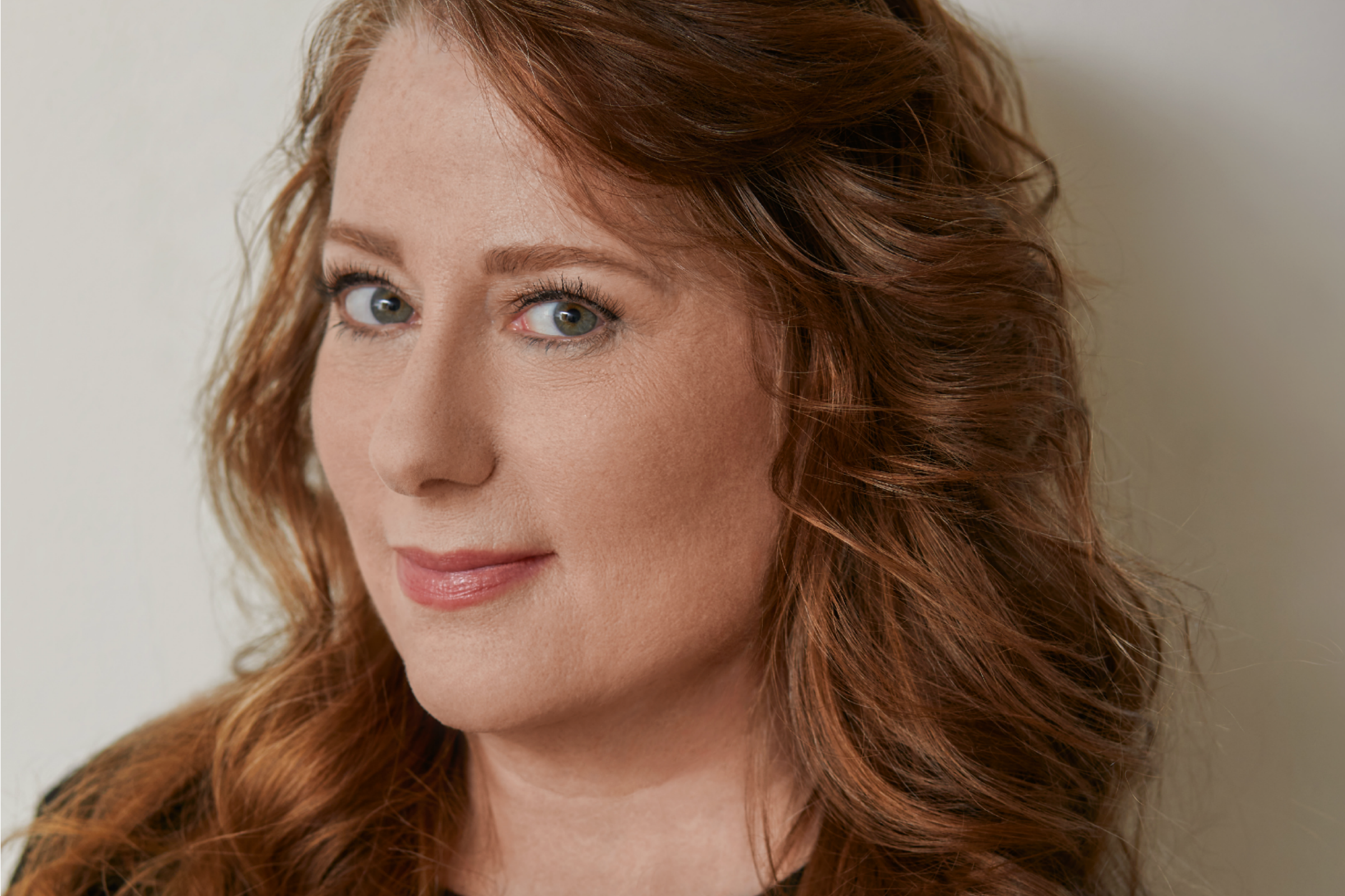 Woman with red hair turns her green eyes toward the camera with a slight smile on her face.