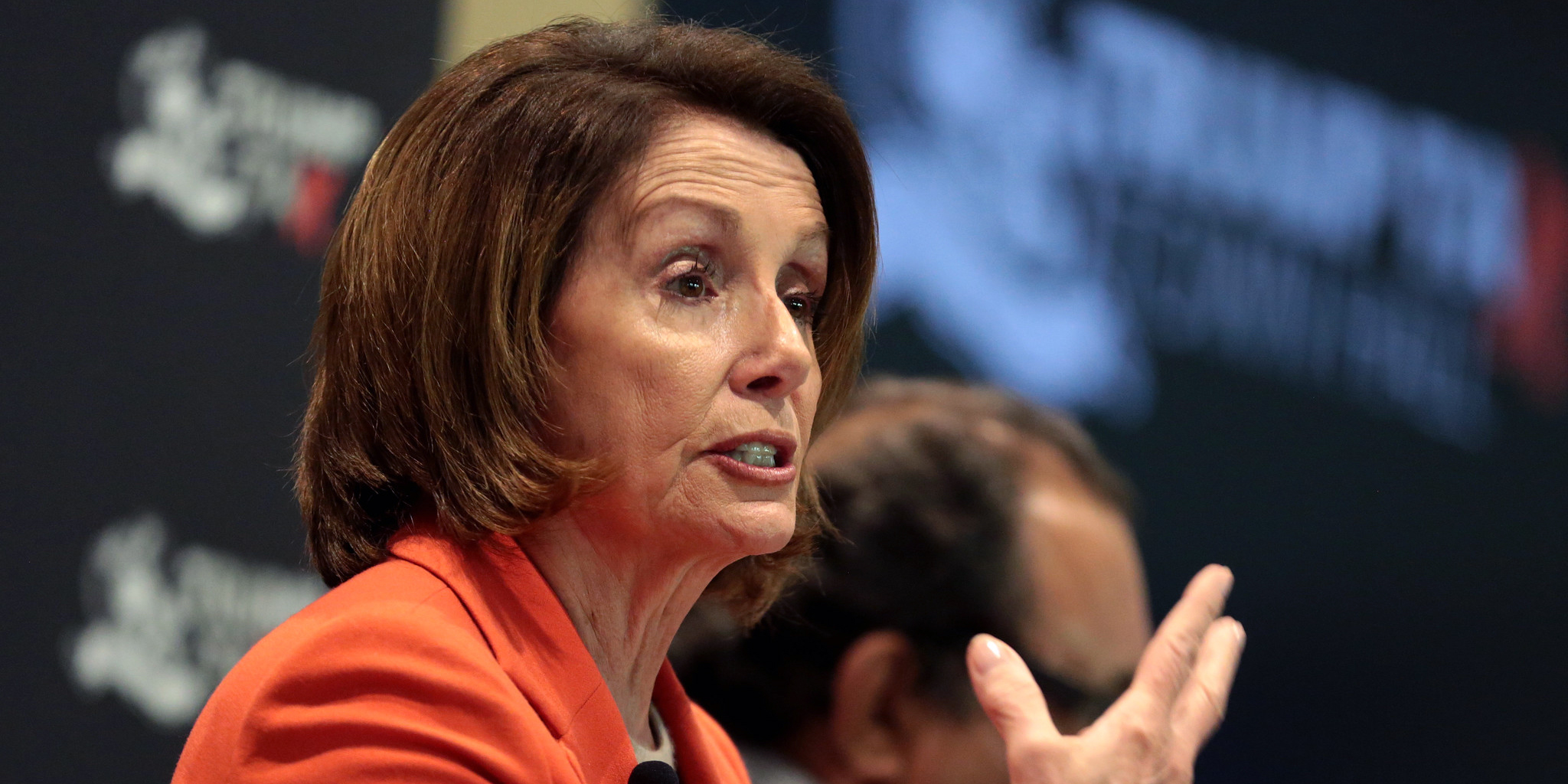 Nancy Pelosi speaking and gesturing with her hand at a town hall