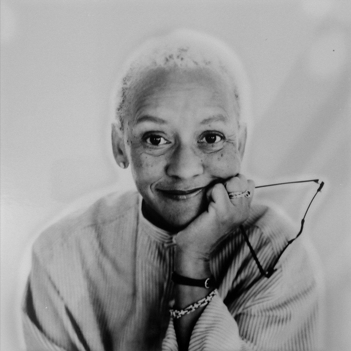 A black and white portrait of Nikki Giovanni, a Black woman with short, blond hair, holds her hand up to her chin