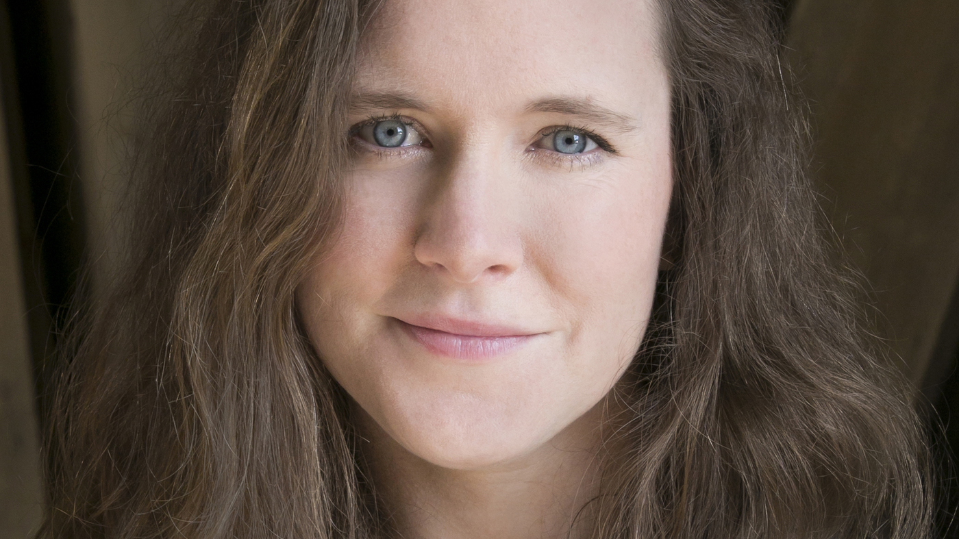 Author Nina MacLaughlin, a white woman with shoulder-length brown hair, smiles for the camera