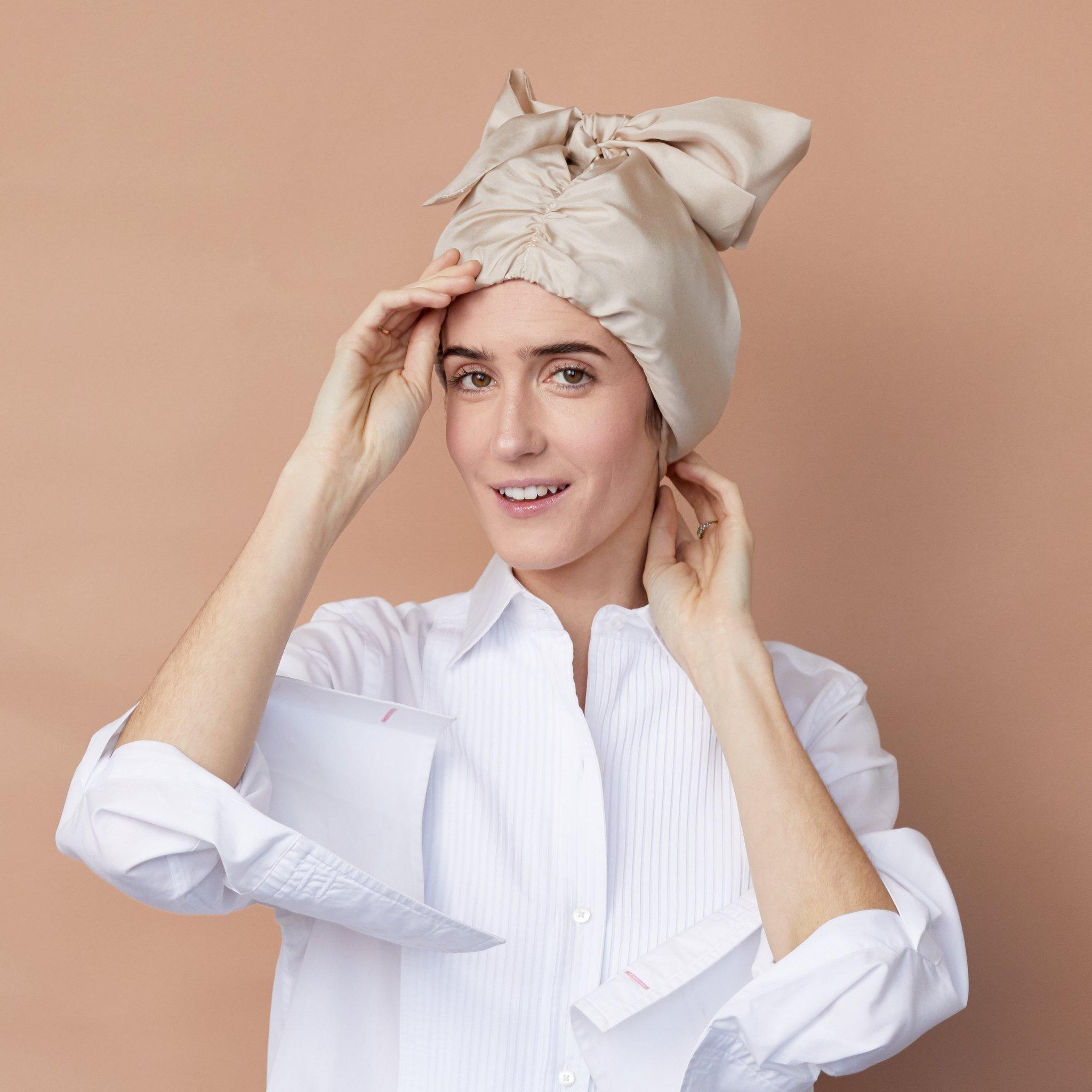 A white woman wears a NiteCap, a silk bonnet.