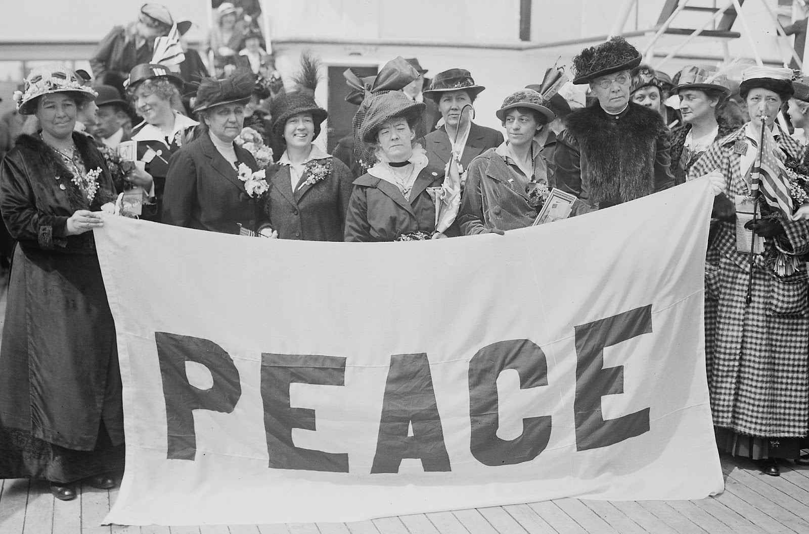 a black and white photo of women protestors in the 1900s holding a large PEACE banner