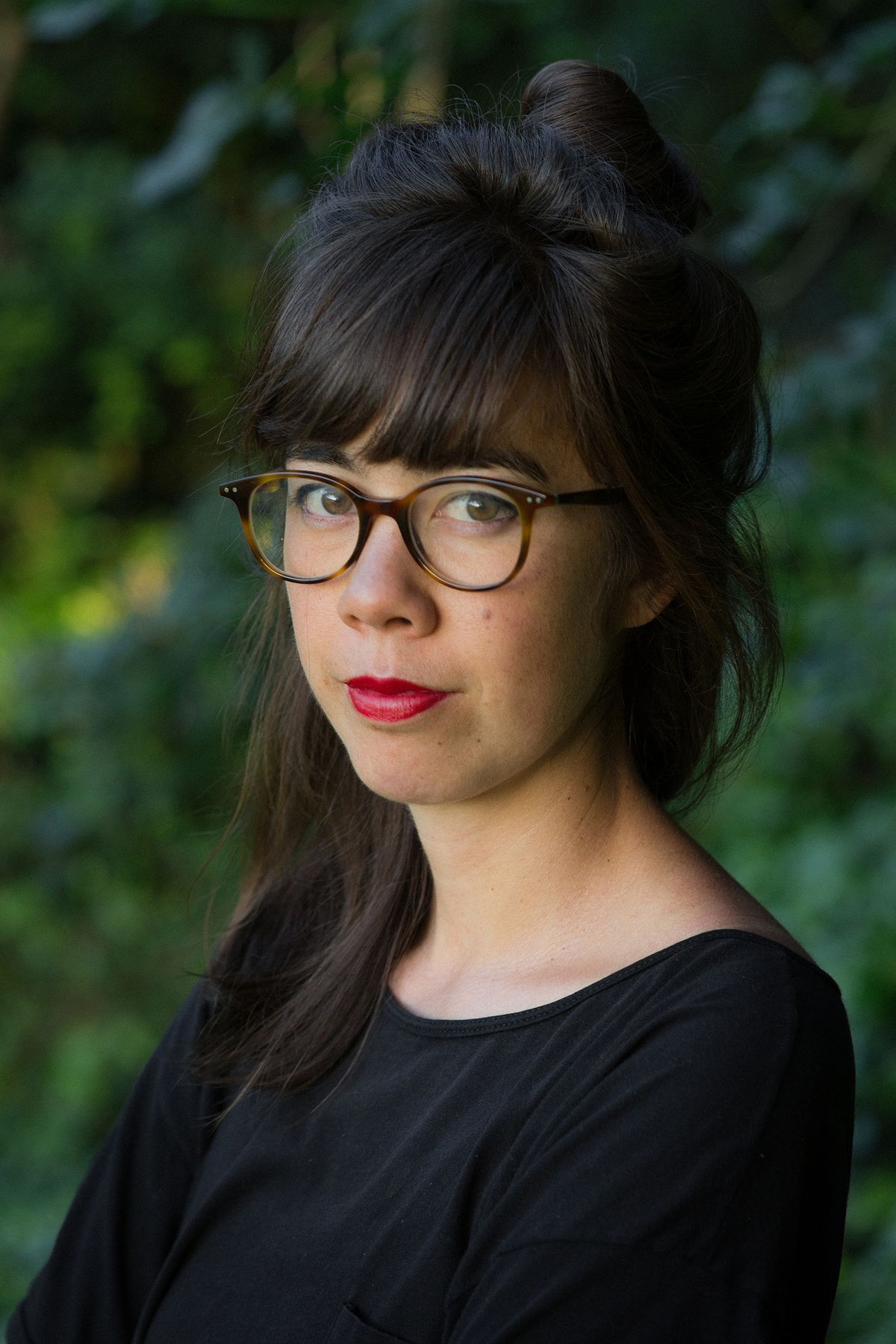 A photo of author Jenny Odell, who has brown hair and bangs and wears glasses while looking straight into the camera and not smiling.