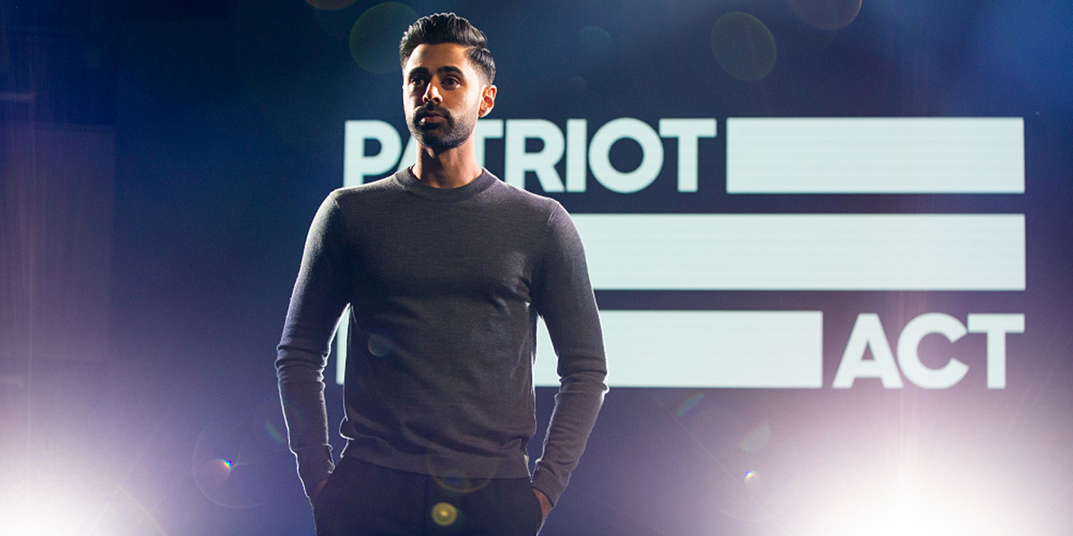 "Hasan Minhaj stands on stage with his hands in his pockets, the words ""Patriot Act"" displayed behind him"