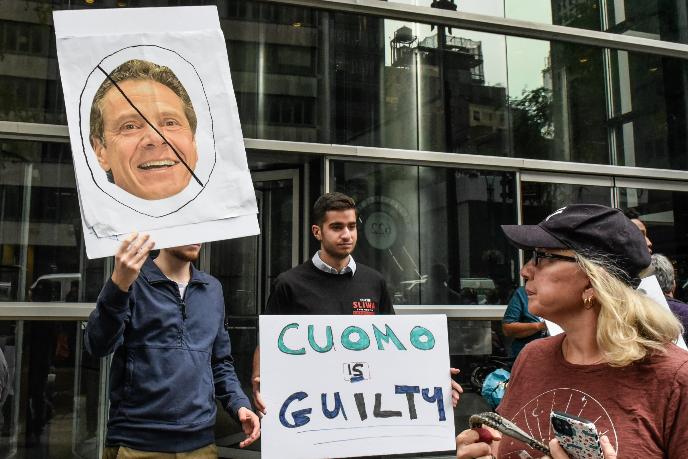 a protestor in a navy blue windbreaker holds up a poster of Andrew Cuomo, an aging white man with short, curly, brown hair, during a protest