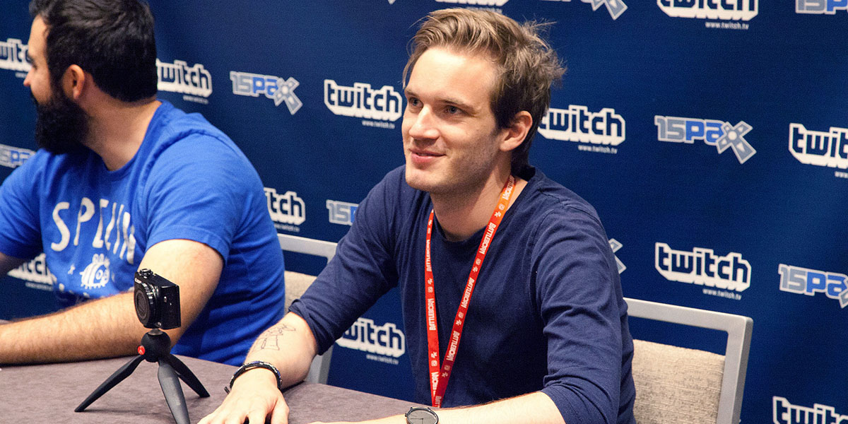 PewDiePie sitting with his hands on a table with a dark haired person next to him and a wall behind him featuring the Twitch logo