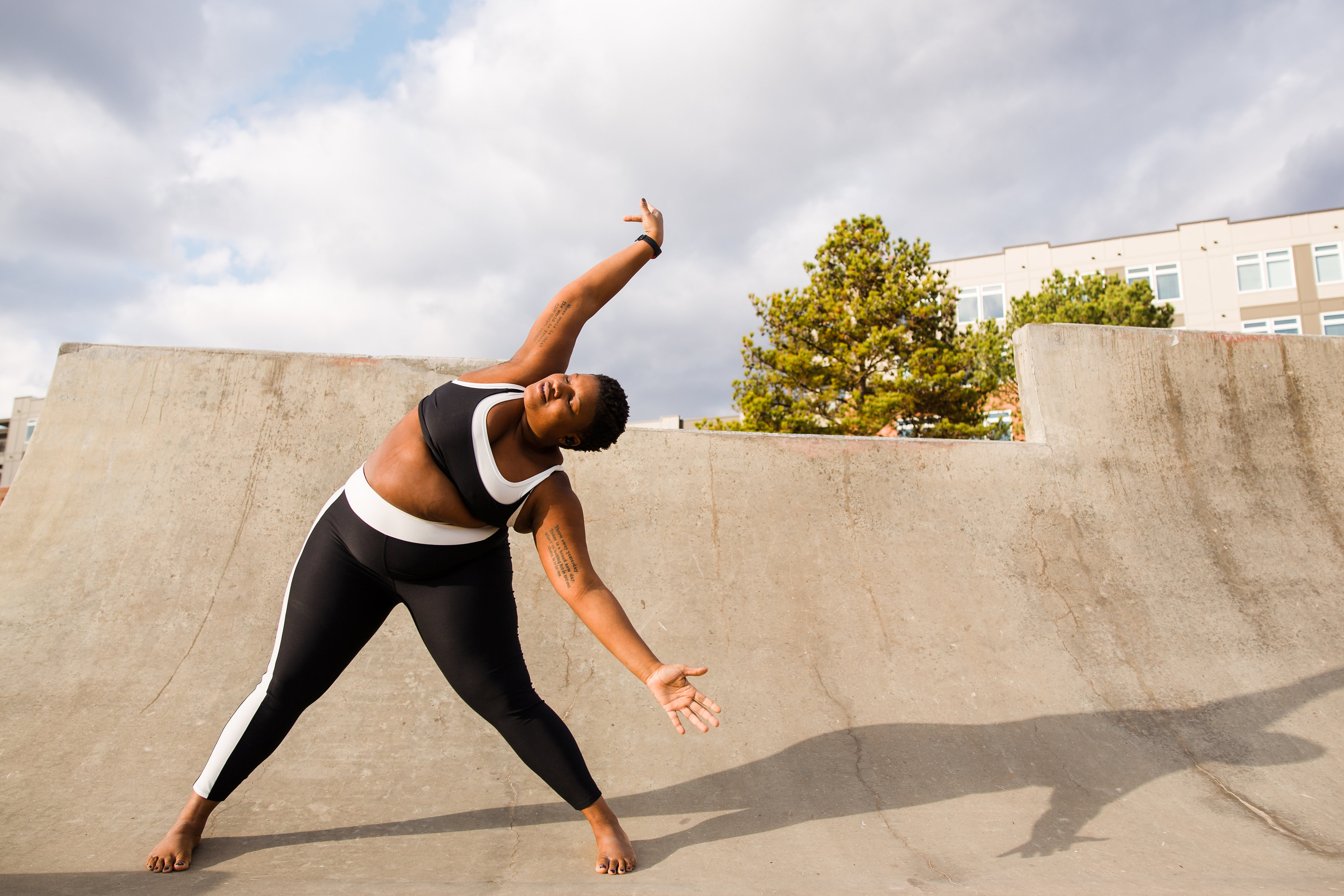 Jessamyn Stanley, a Black yogi with short, natural black hair, does yoga outside. She wears a crop top and leggings and the sun is soft behind her.