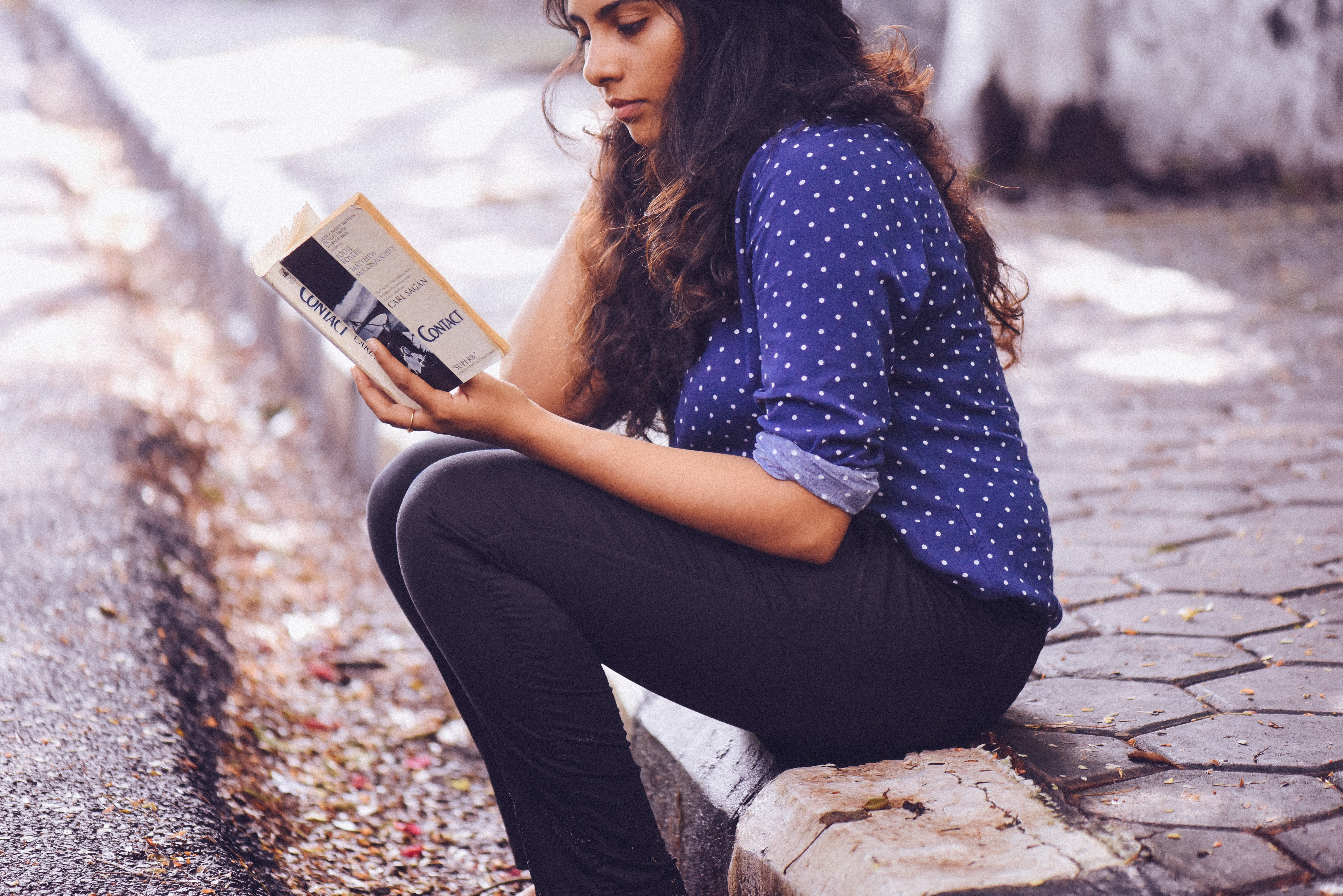 an Indian teenage girl sits on the curb, holding a white and black book in her hands