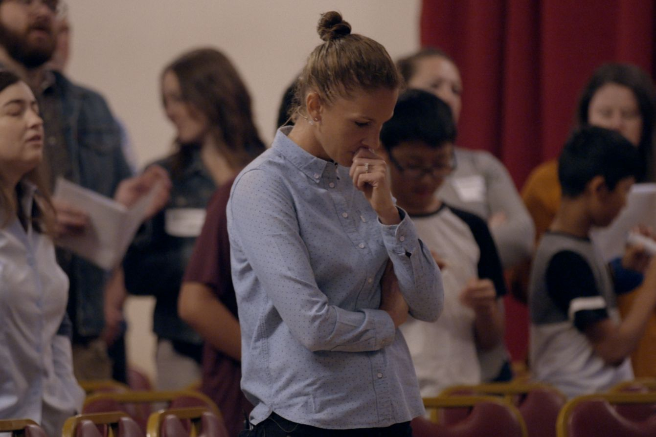 Julie Rodgers, a thin, white woman with her blond hair pulled into a ponytail and wearing a light-blue collared shirt, looks down in a church pew in Pray Away