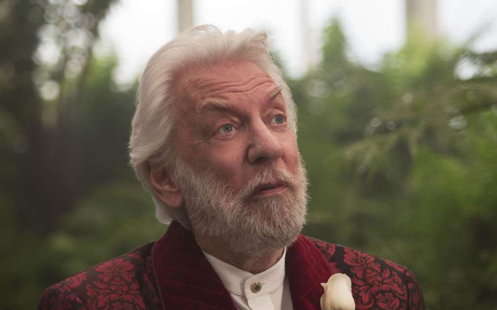 Donald Sutherland as President Snow, looking up with a vacant expression, wearing a maroon suit with a white rose in his pocket