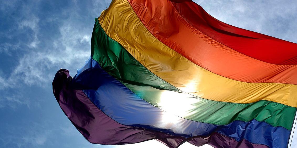 The rainbow Pride flag flying against a blue sky