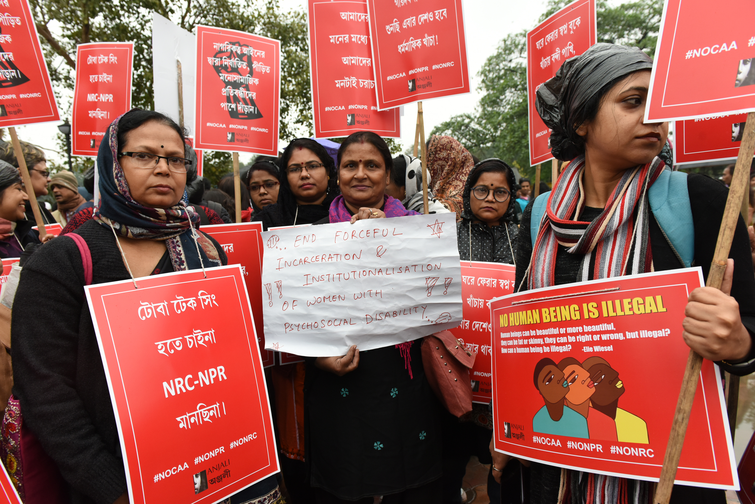 a group of Indian women protestors hold burgundy signs that reflect their protest