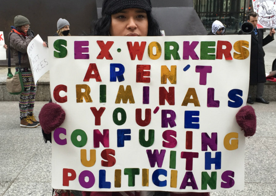 Protestor holding sex work is work sign