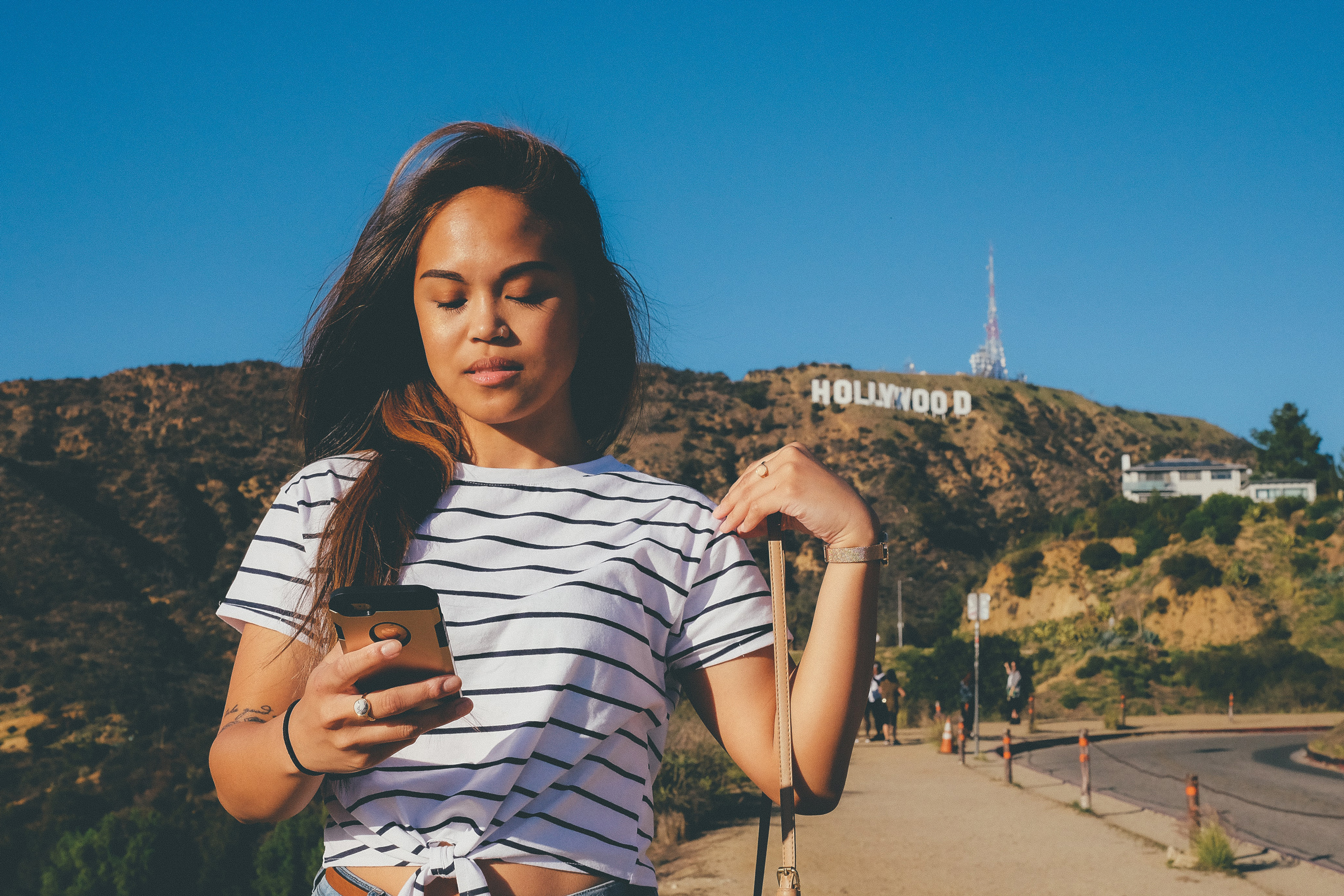 a woman of color with dark hair looks down at her phone, the Hollywood sign behind her