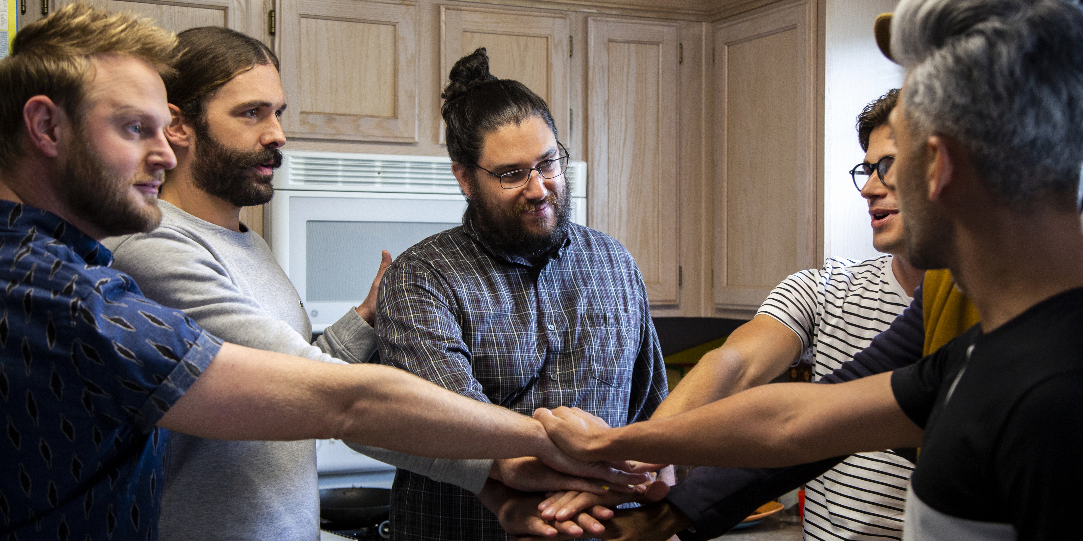 The fab five put their hands together with a male subject in his kitchen