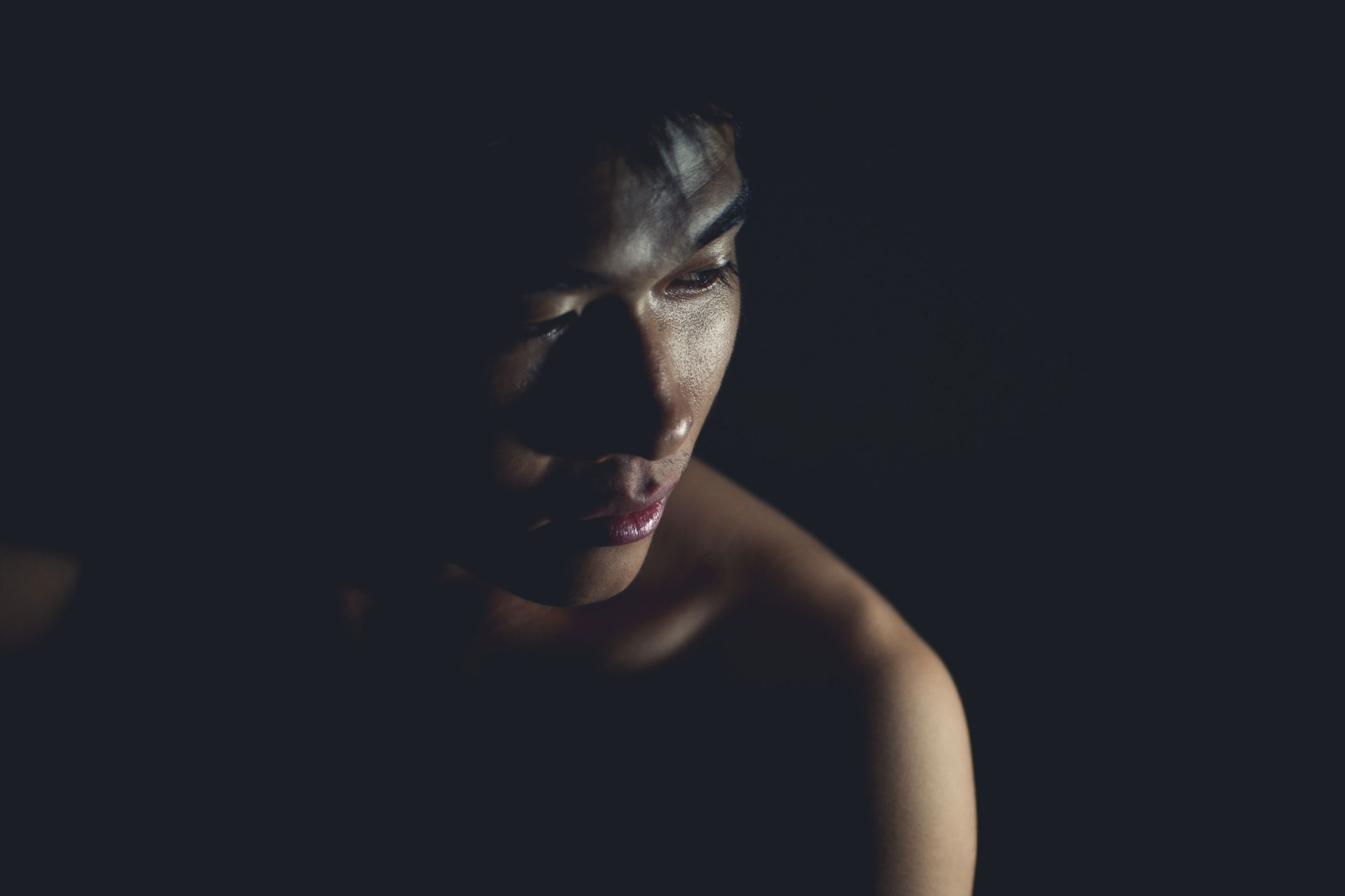 a somber image of an Asian person shrouded in darkness and looking away from the camera