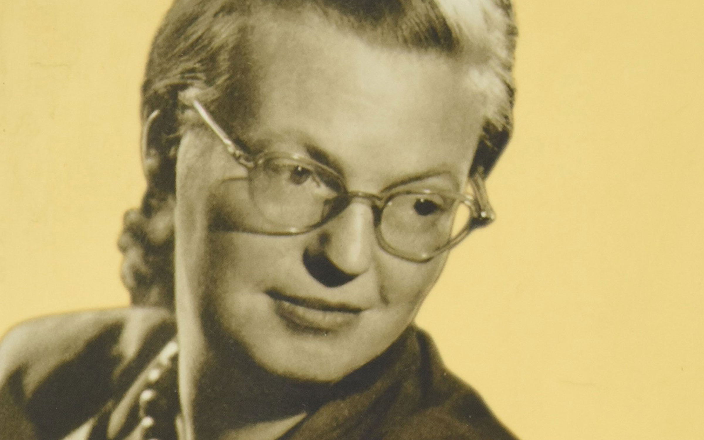 Shirley Jackson, a white woman with her blond hair in a bun and wearing glasses, looks downward in front of a yellow background