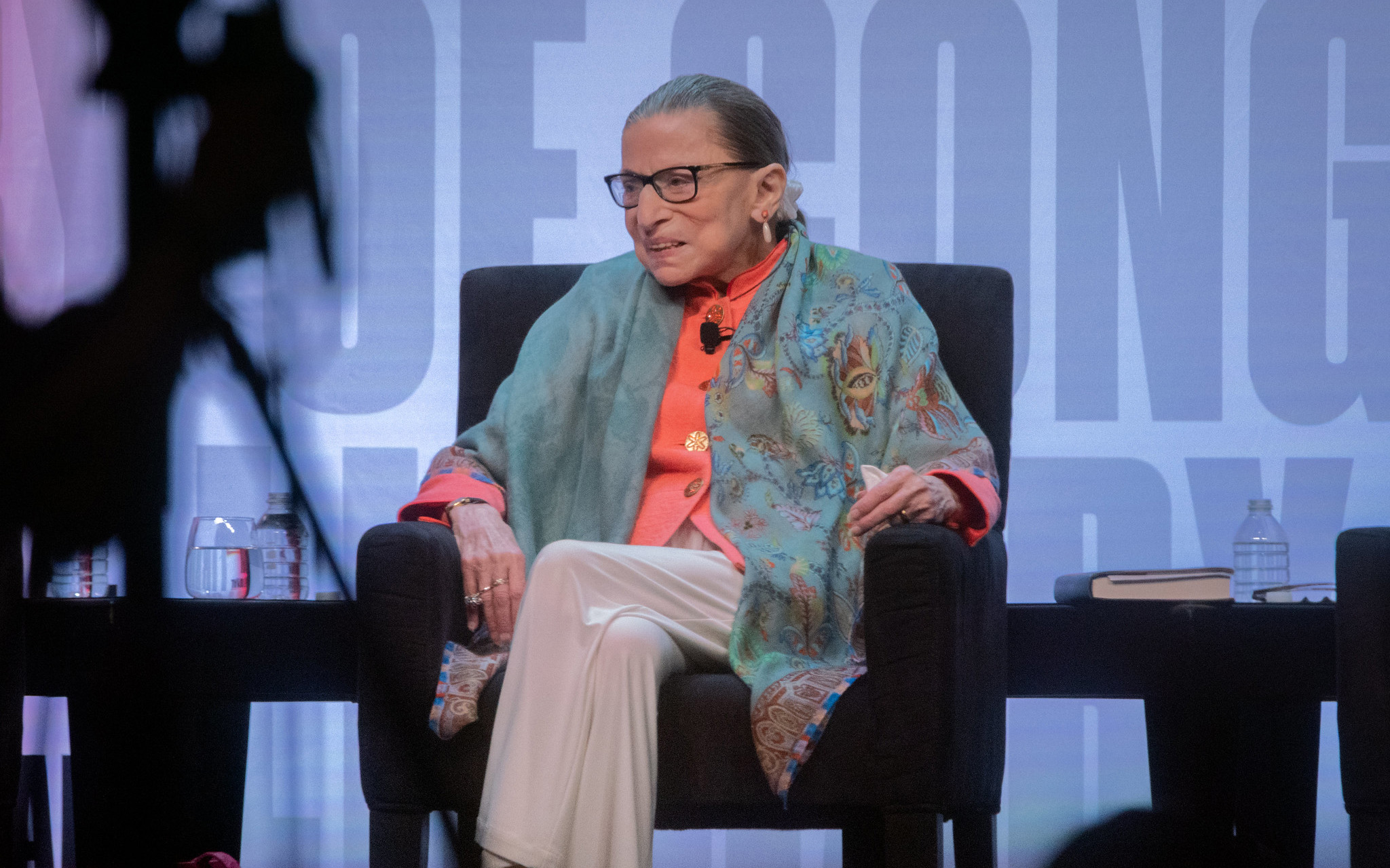 Ruth Bader Ginsburg, an old white woman with brown hair, wears glasses and a loose shawl and sits on stage while smiling.
