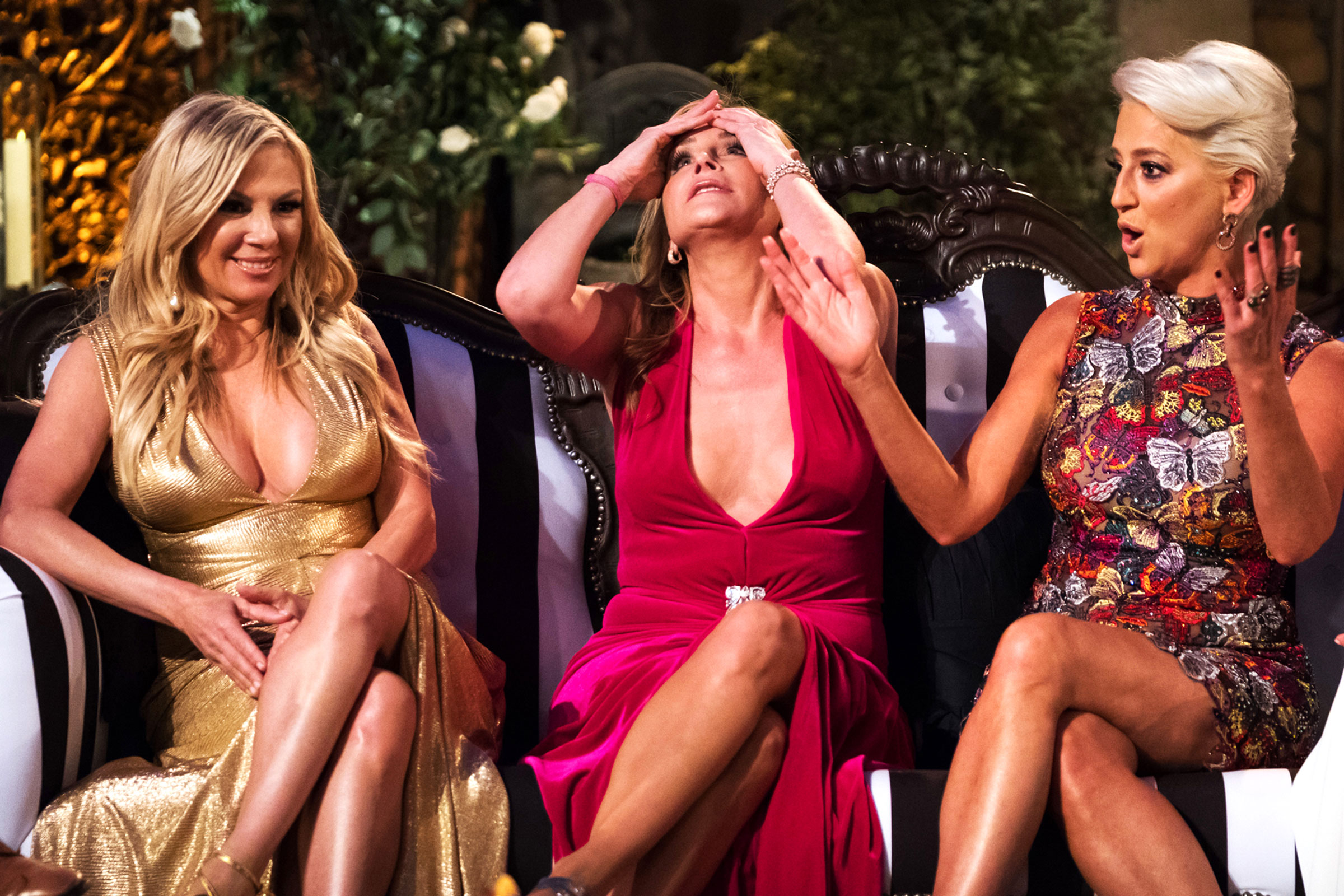 Three rich looking white women wearing fancy dresses who all have blond hair and are arguing and looking stressed.