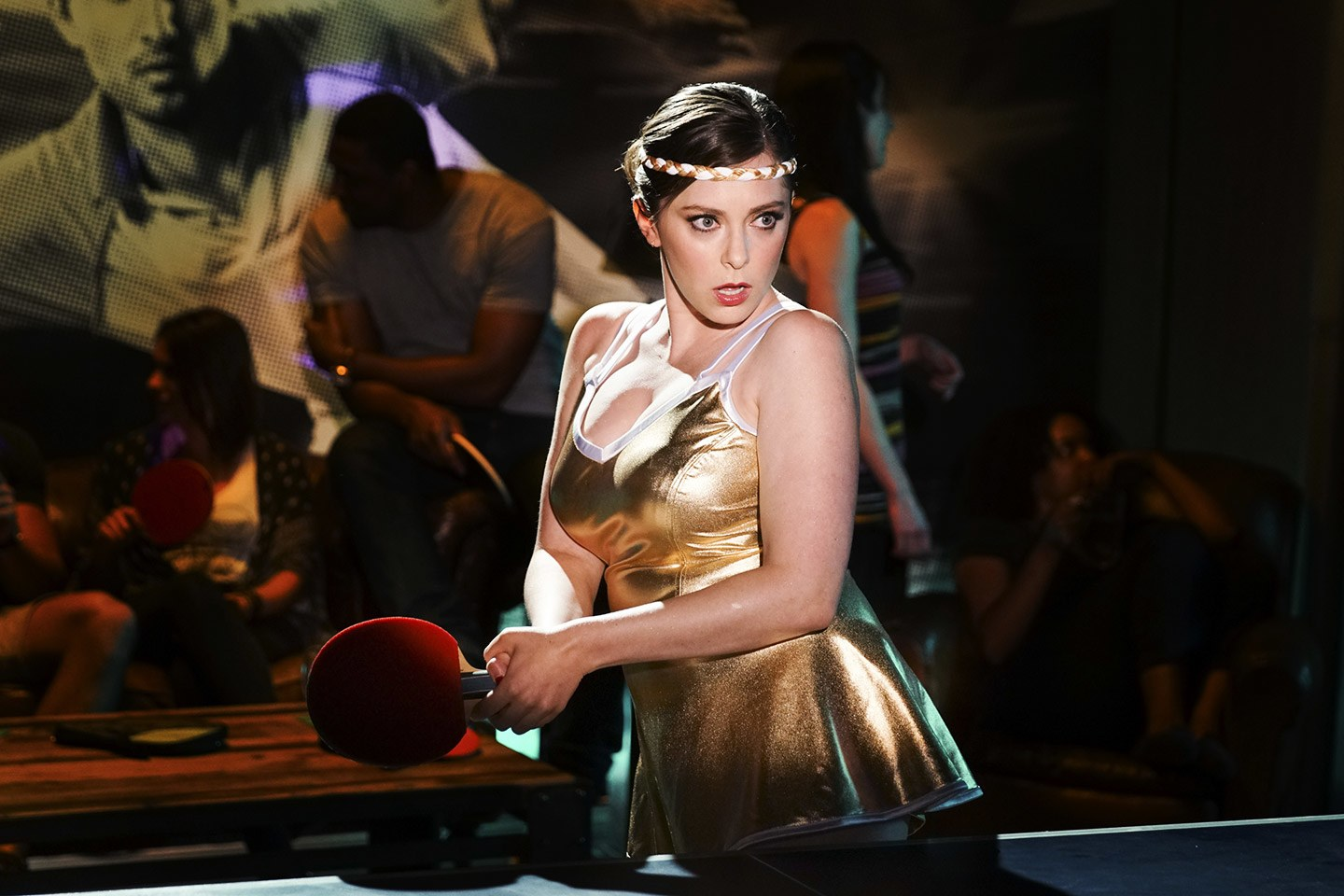 a photo of actress Rachel Bloom, a white woman with brown hair, wearing a gold dress and a gold headband