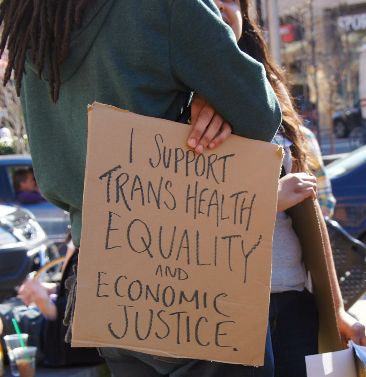 a Black person with locs holding a I Support Trans Equality, Healthcare, and Economic Justice cardboard sign at a rally
