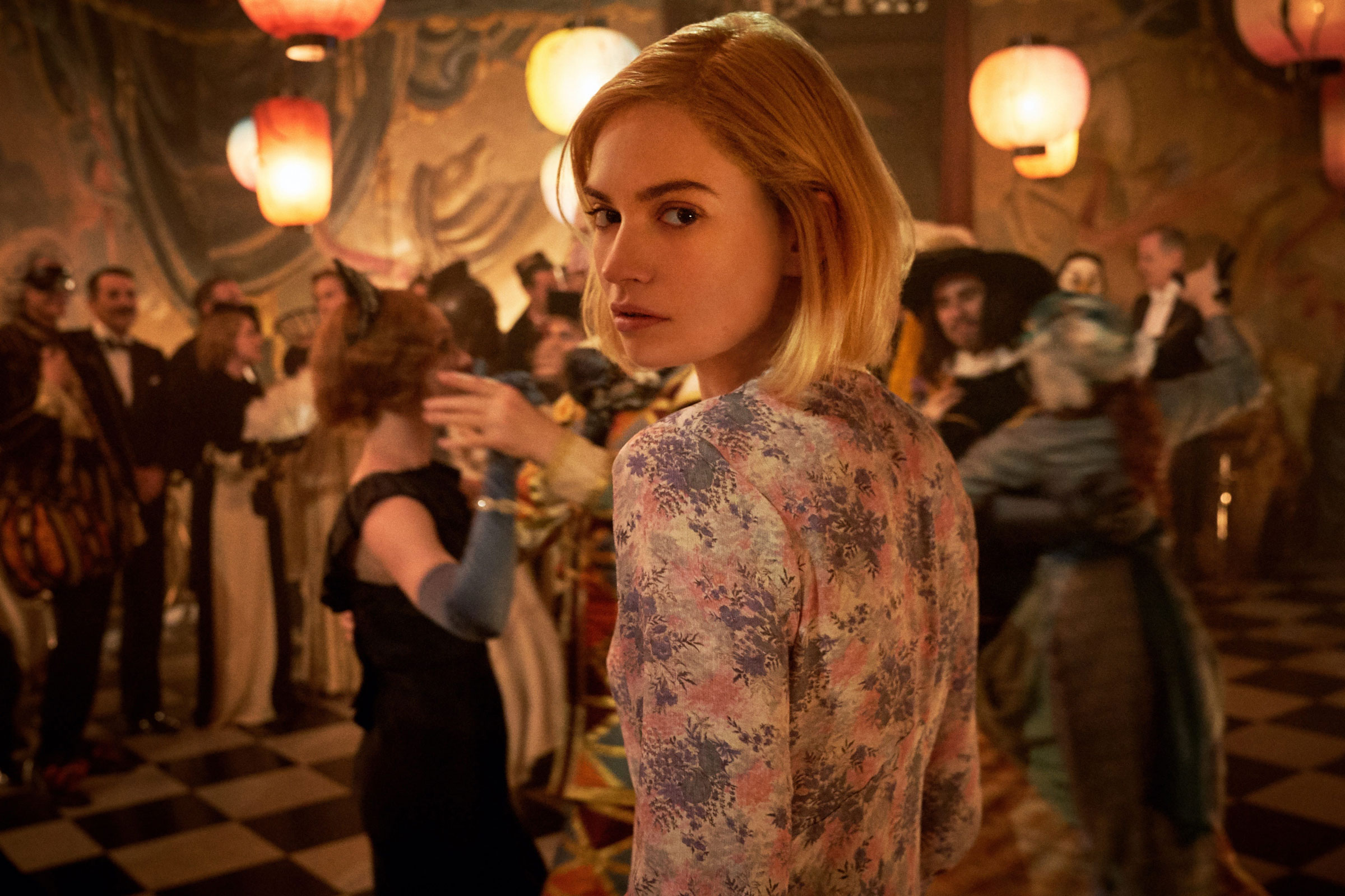 Lily James plays Mrs. de Winter, a woman with shoulder-length blond hair looking over her shoulder, in Rebecca