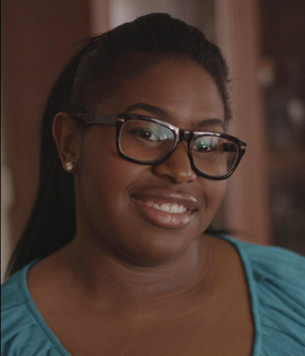 Rebekah Weatherspoon, a Black woman wearing glasses, smiles at the camera