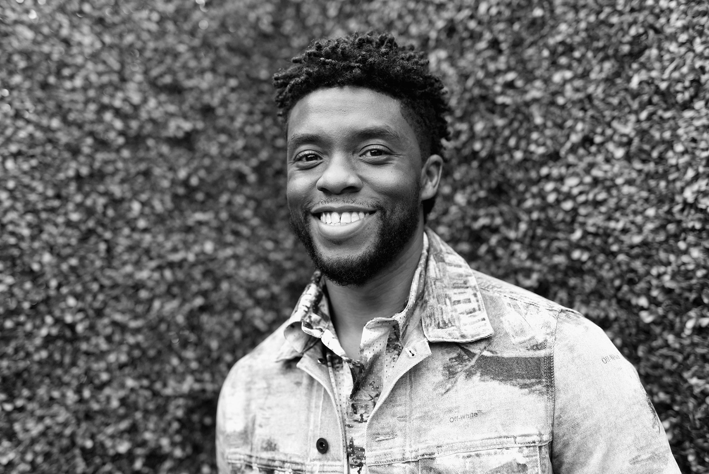 Chadwick Boseman, a Black man with short, black hair, smiles broadly at the camera
