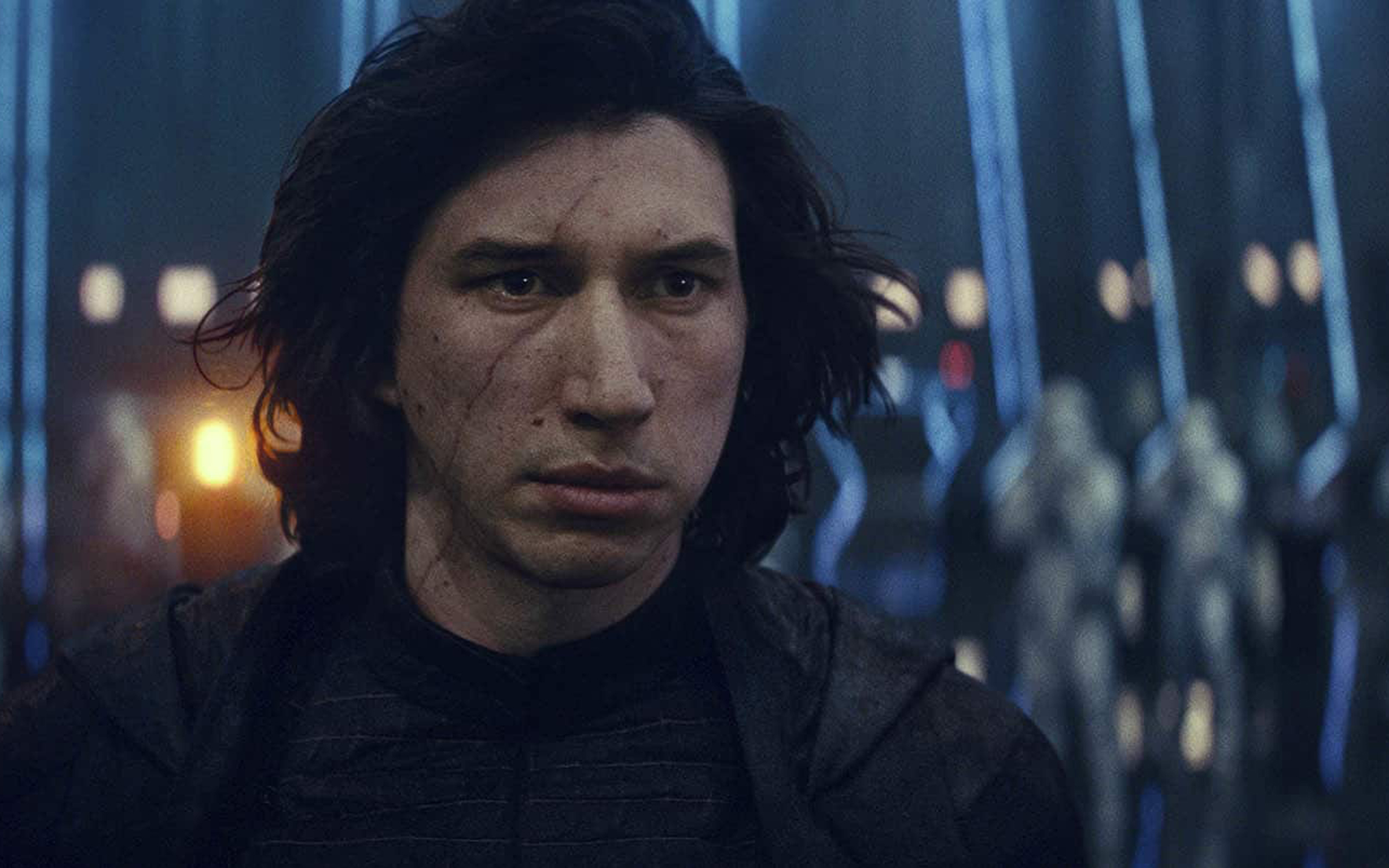 A closeup of Adam Driver's face, looking mopey, with Storm Troopers in the background